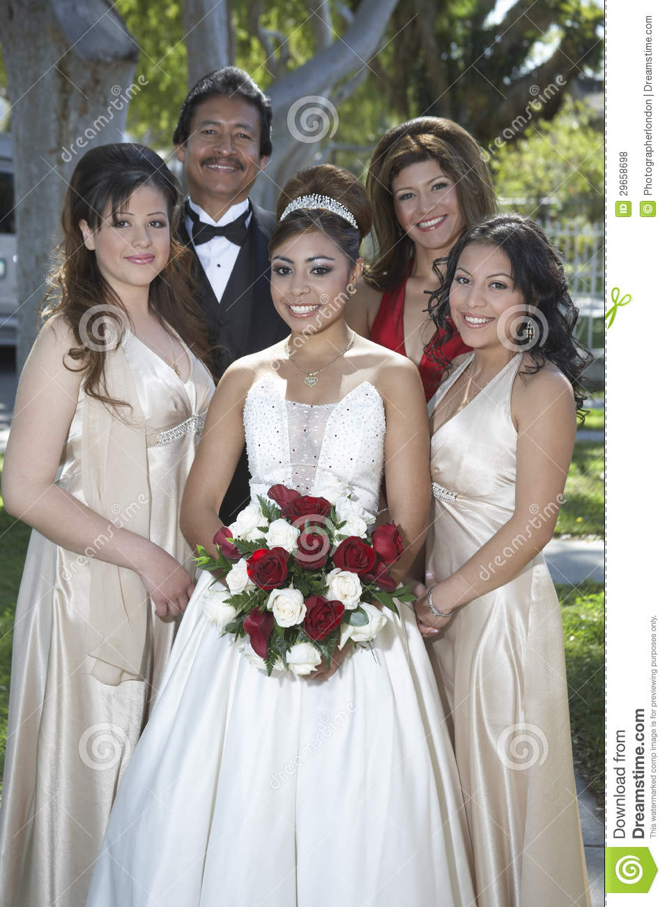 Quinceanera Standing With Parents And Friends In Lawn