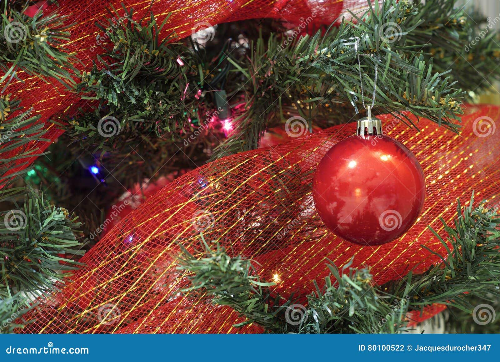 Quinquilharia vermelha do Natal com fita em uma árvore