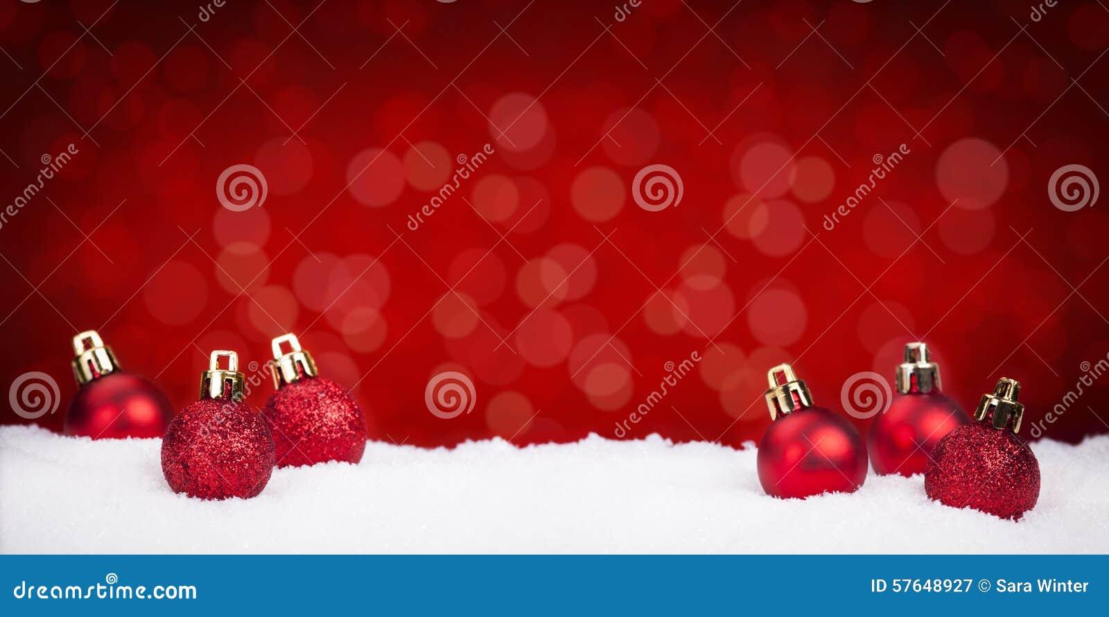 Quinquilharias vermelhas do Natal na neve com um fundo vermelho