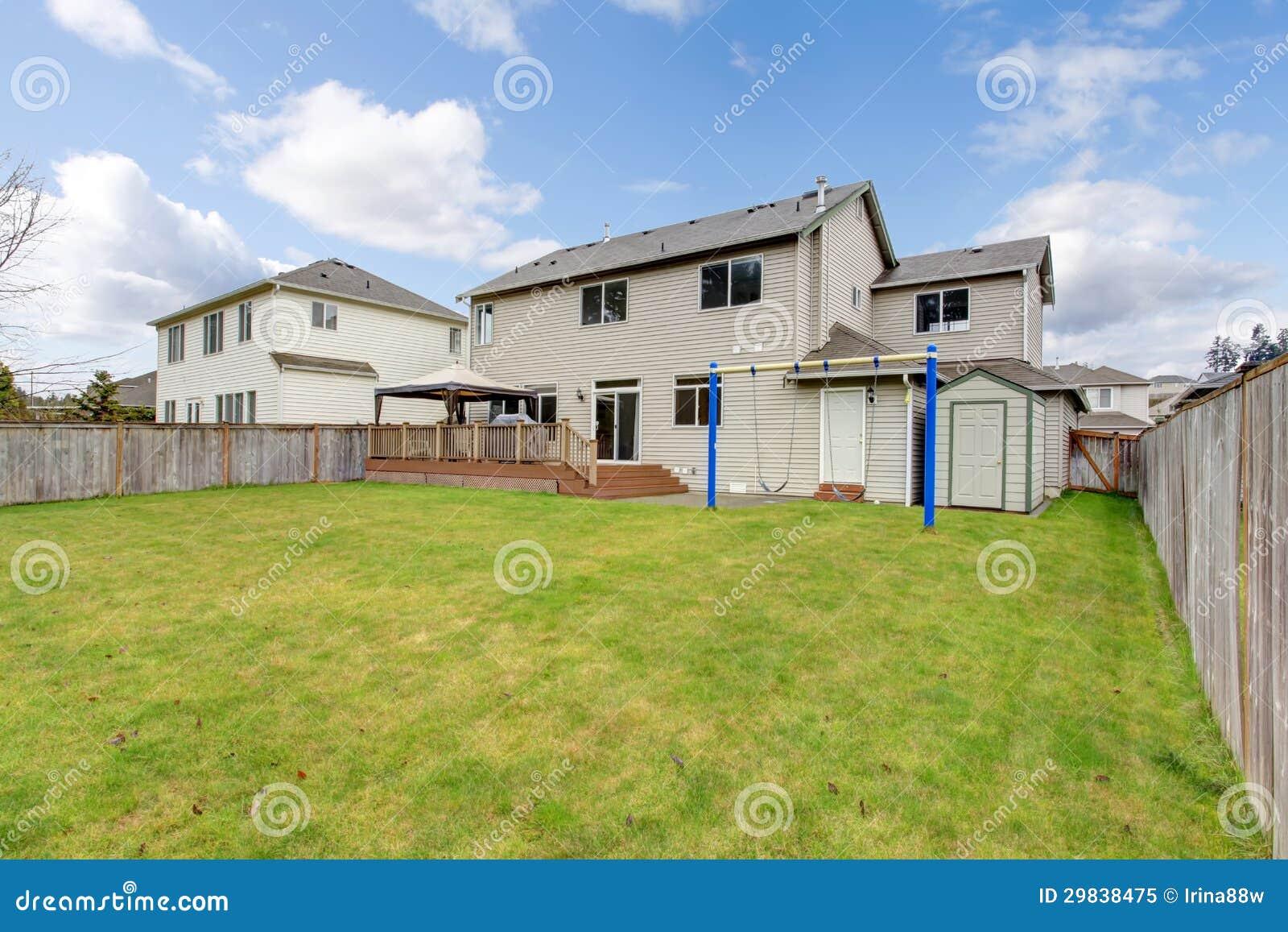 Quintal com a casa e a cerca americanas típicas.