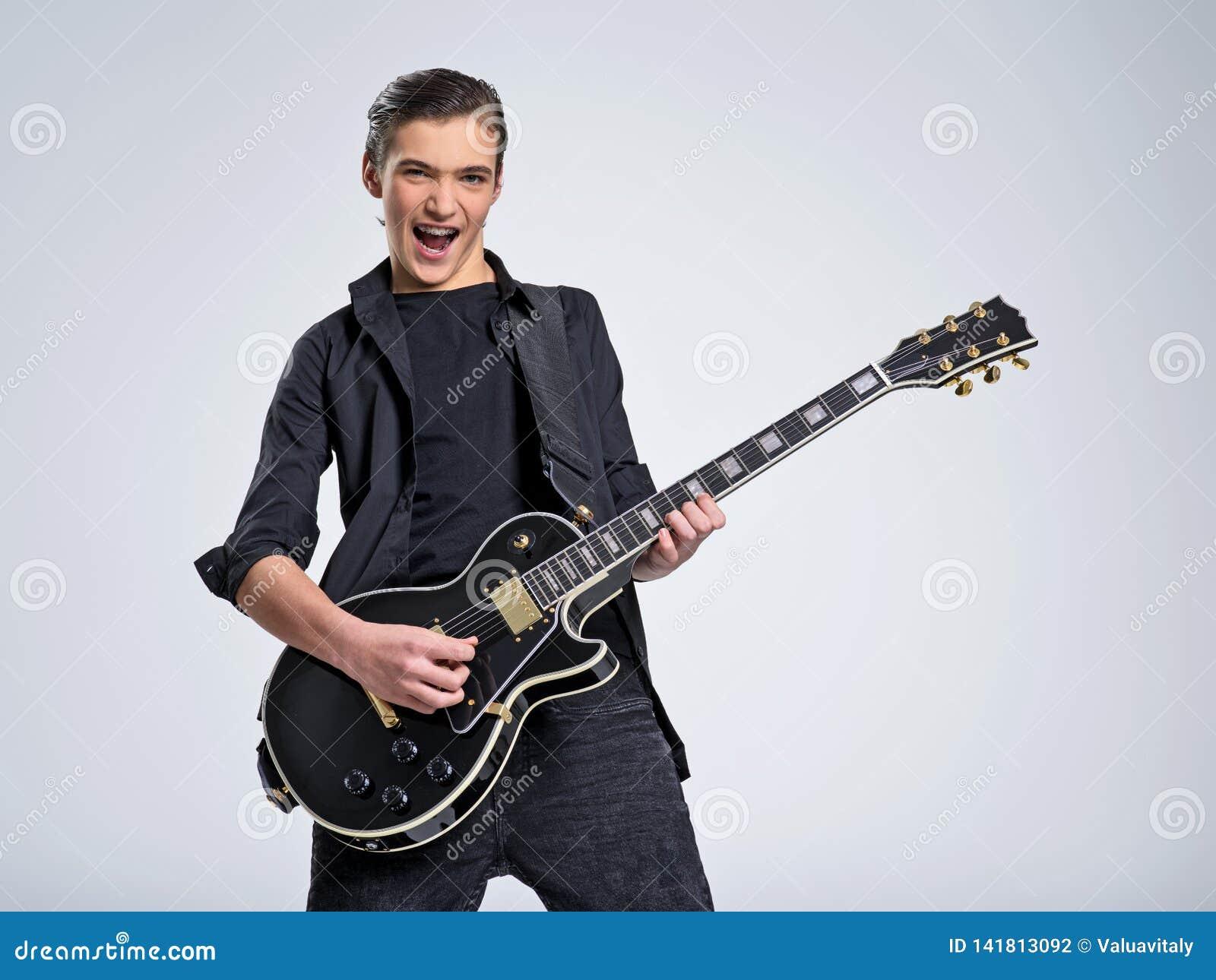 Quinze anos de guitarrista idoso com uma guitarra elétrica preta O músico adolescente guarda a guitarra