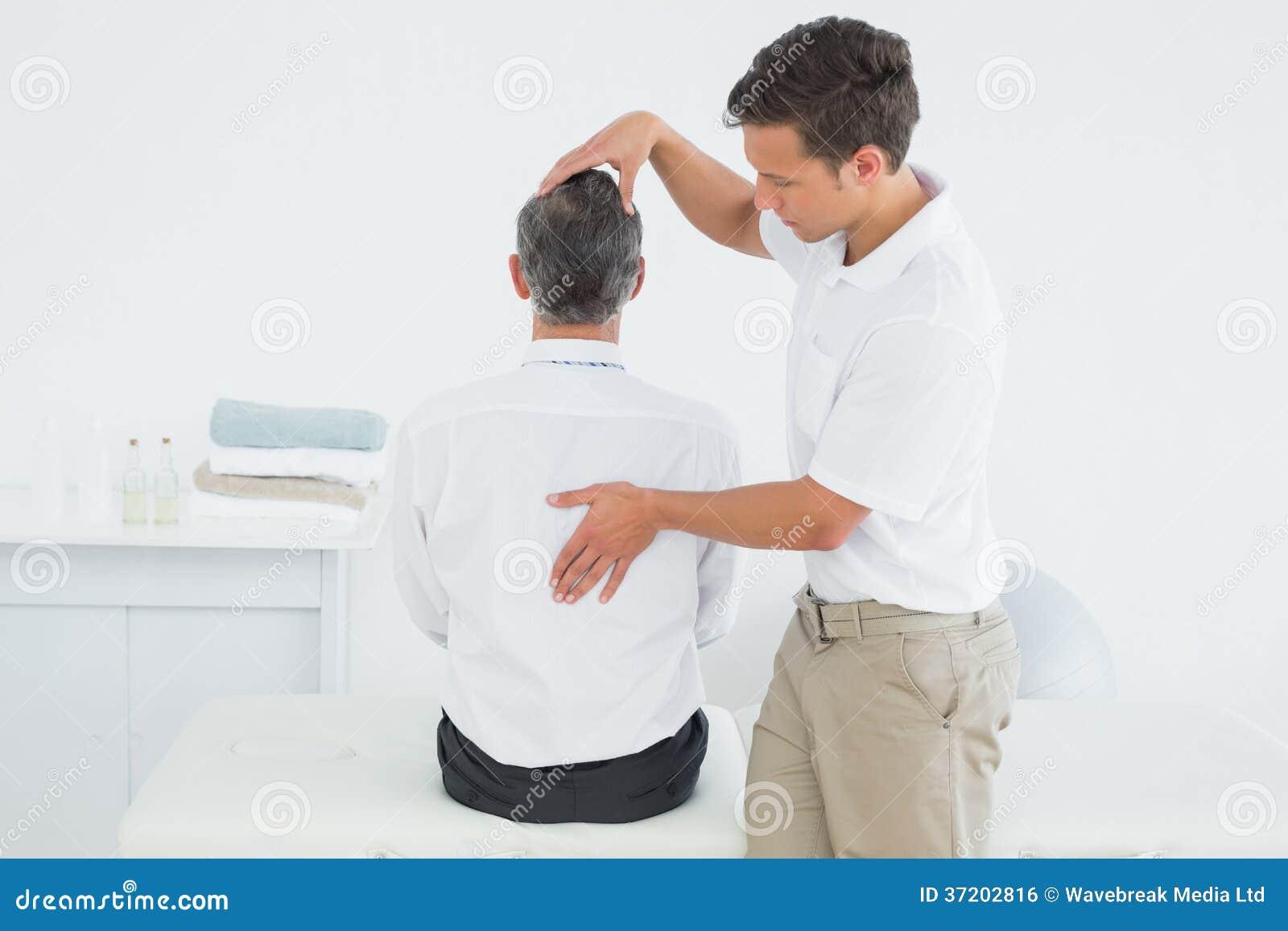 Quiroprático masculino que examina o homem maduro