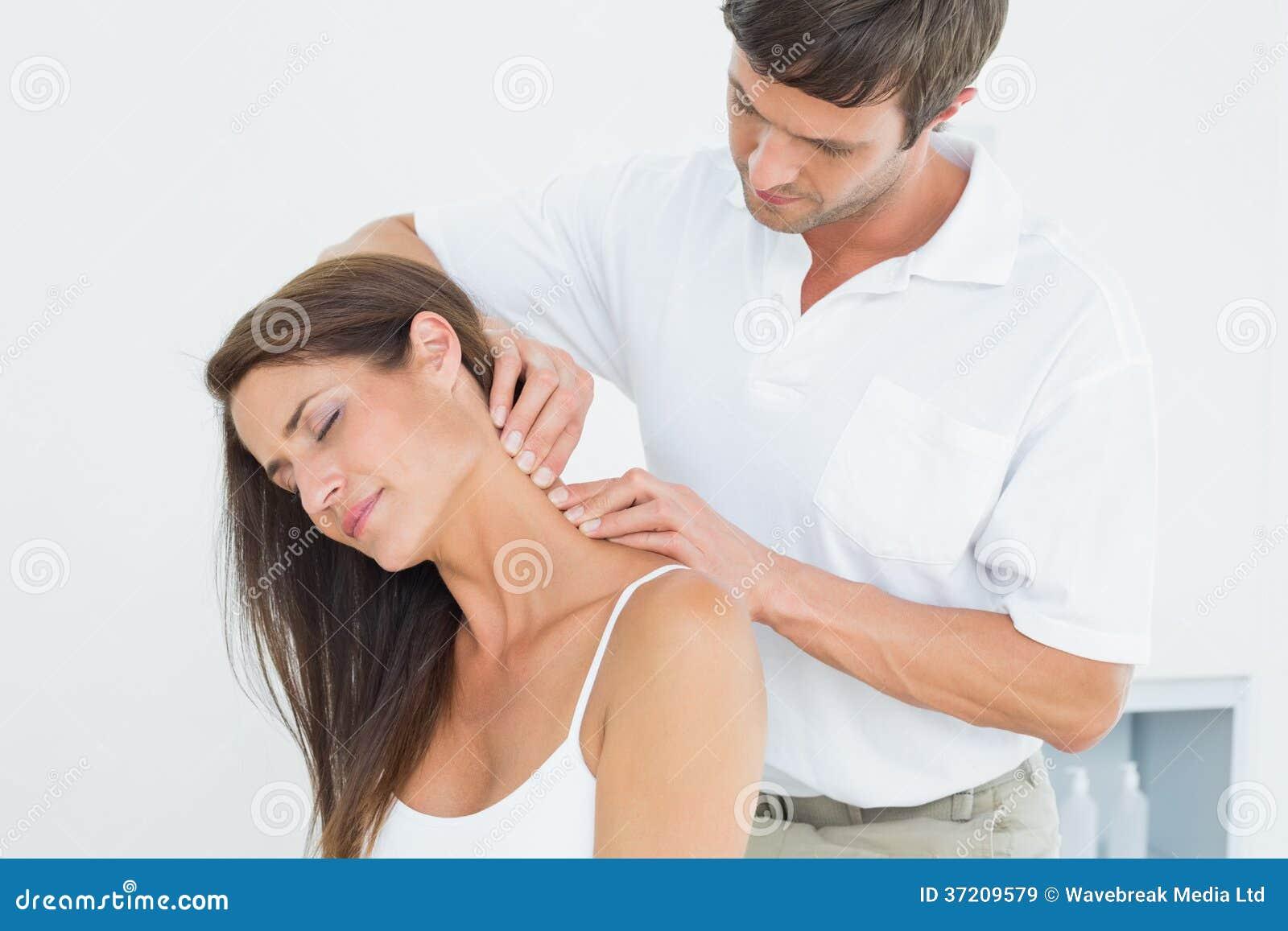 Quiroprático masculino que faz massagens o pescoço de uma jovem mulher