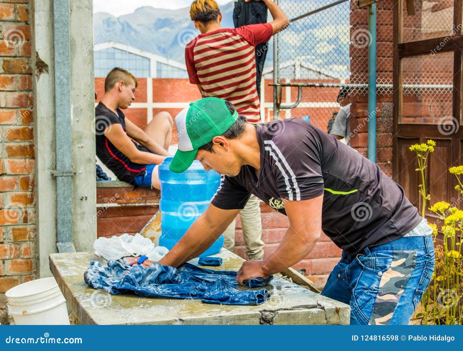 QUITO, ECUADOR, EL 21 DE AGOSTO DE 2018: Opinión al aire libre los individuos jovenes no identificados que lavan la ropa dentro d