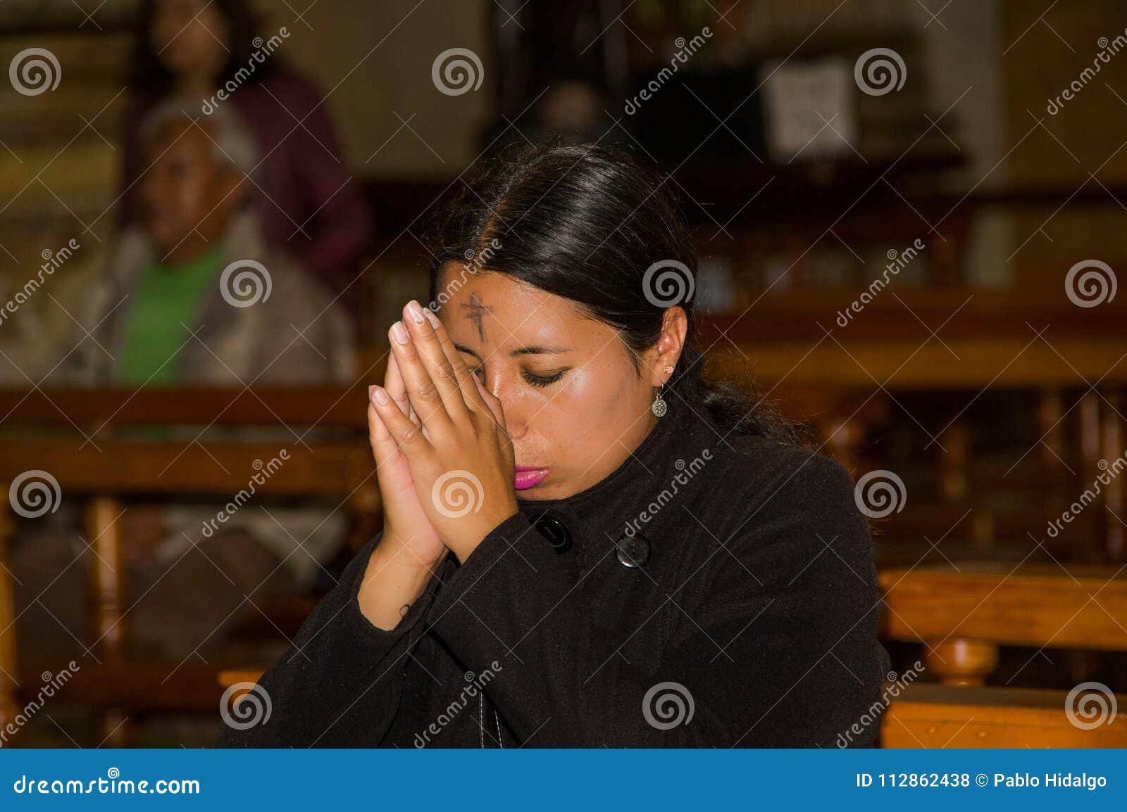 QUITO, ECUADOR, EL 22 DE FEBRERO DE 2018: Opinión interior la gente no identificada que ruega dentro de la iglesia de Catedral de