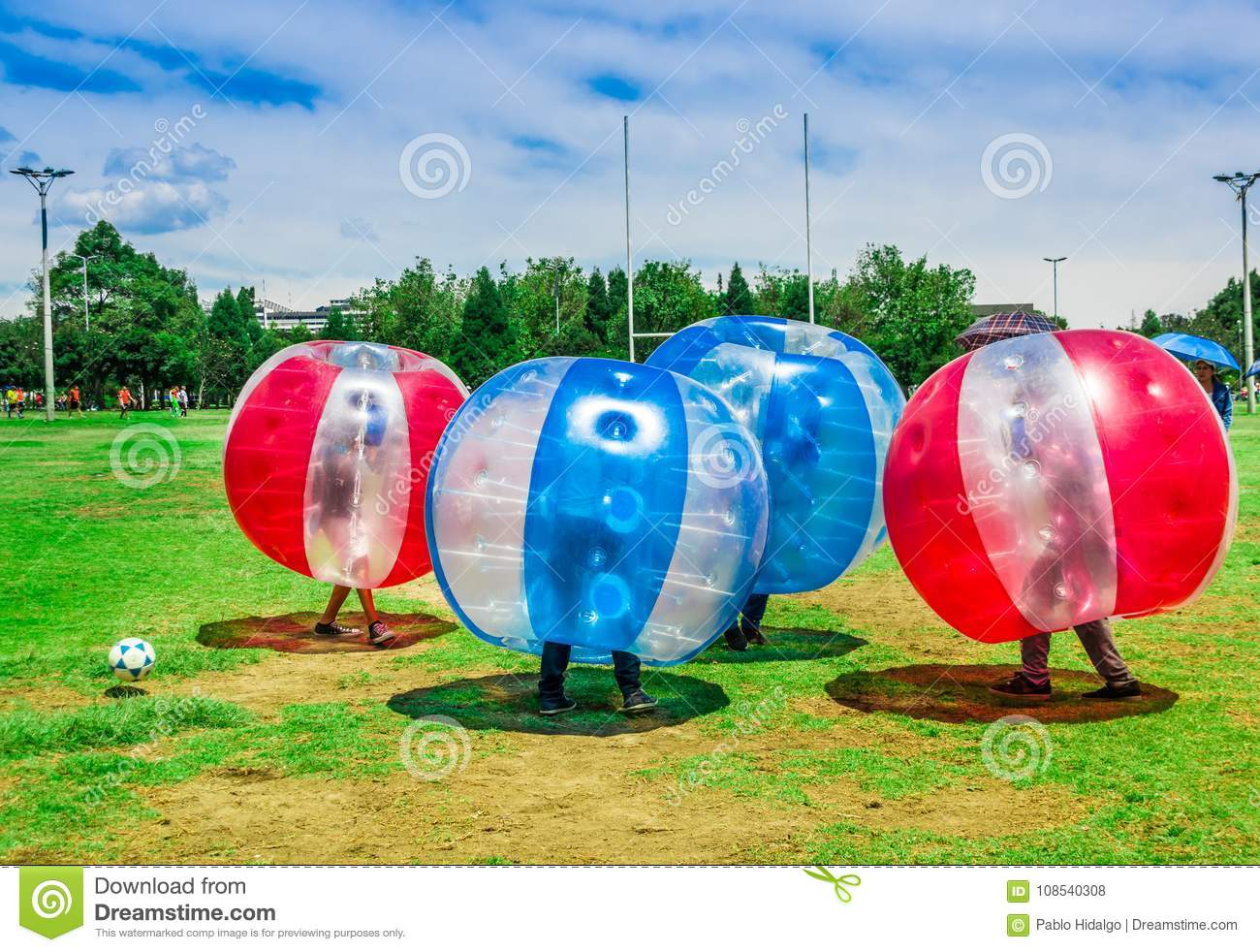 QUITO, ECUADOR - NOVEMBER 28, 2017: Young people playing soccer while is inside of giant inflatable balls in the