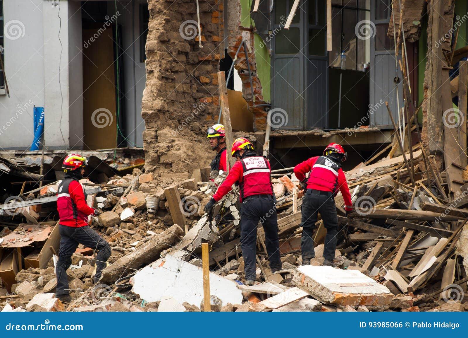 Quito, Equador - 9 de dezembro de 2016: Um grupo não identificado de firemans, limpando a área de dano e a destruição, restos