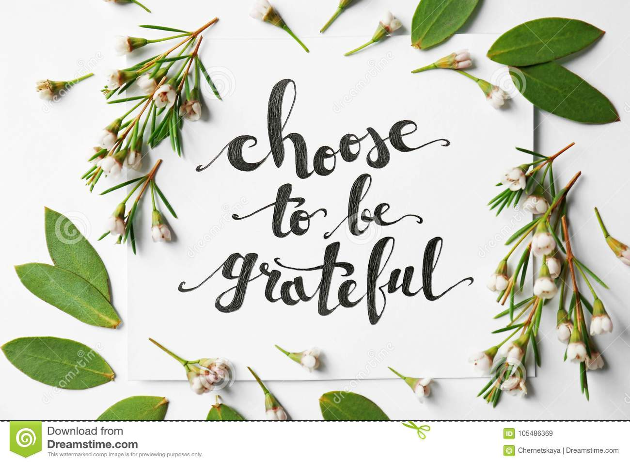 Quote `Choose to be grateful` written on paper with leaves and flowers on white background