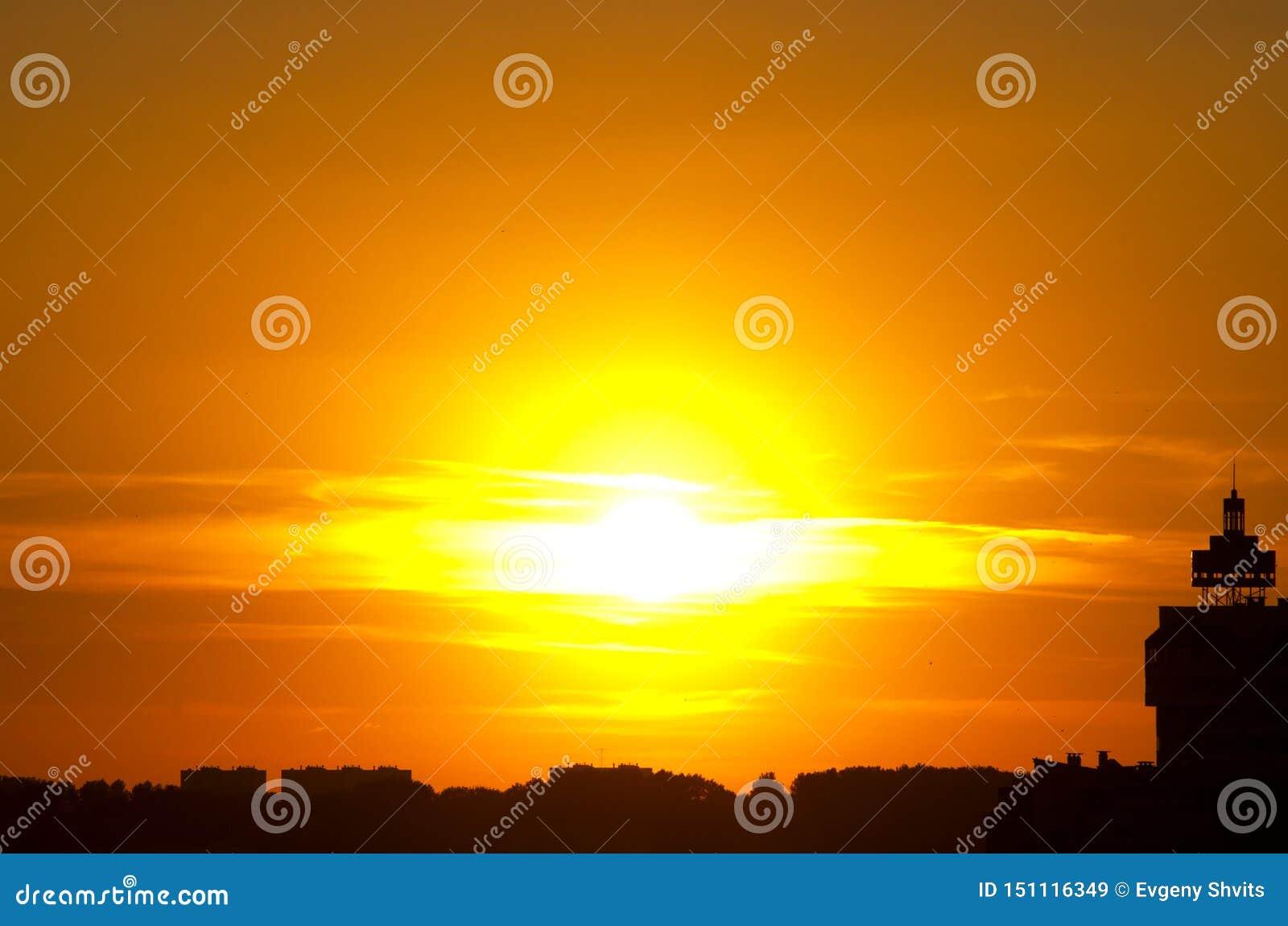 Ráfaga solar de la puesta del sol roja, sol en las nubes, silueta de la ciudad