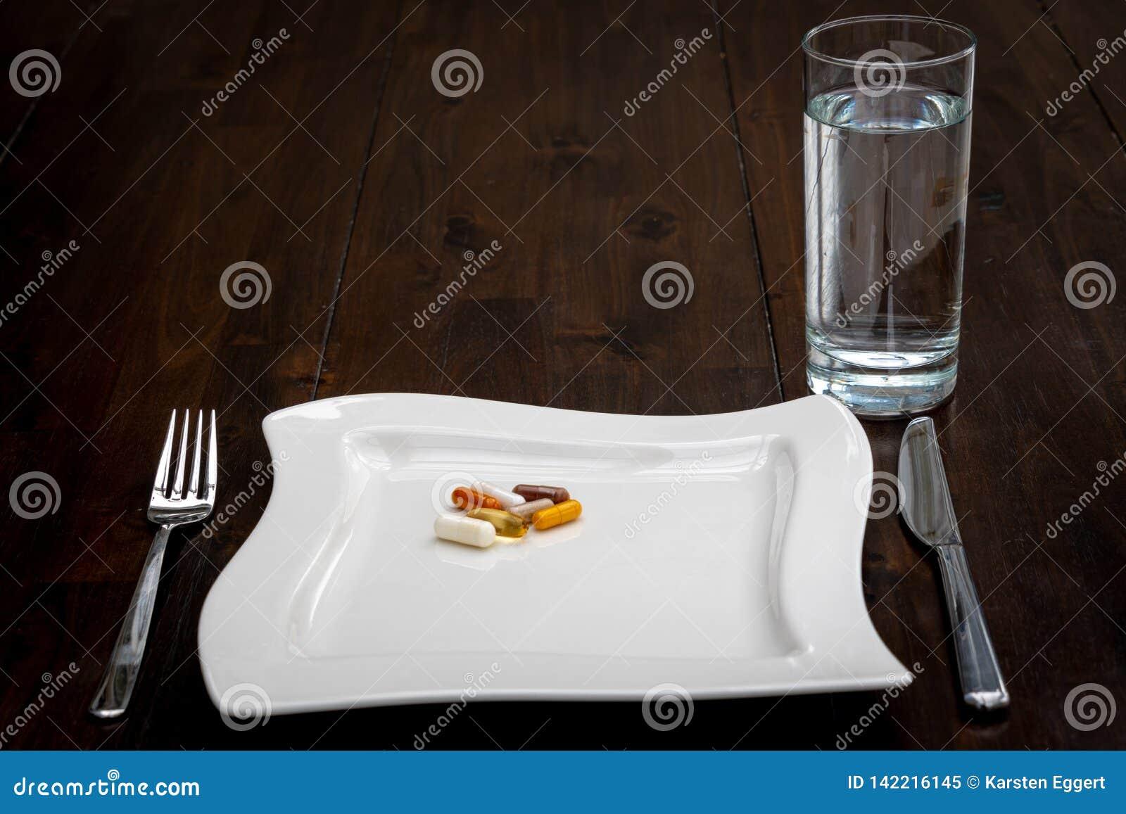 Różnorodne pigułki są na białych talerzach obok szkła woda na brązu stole