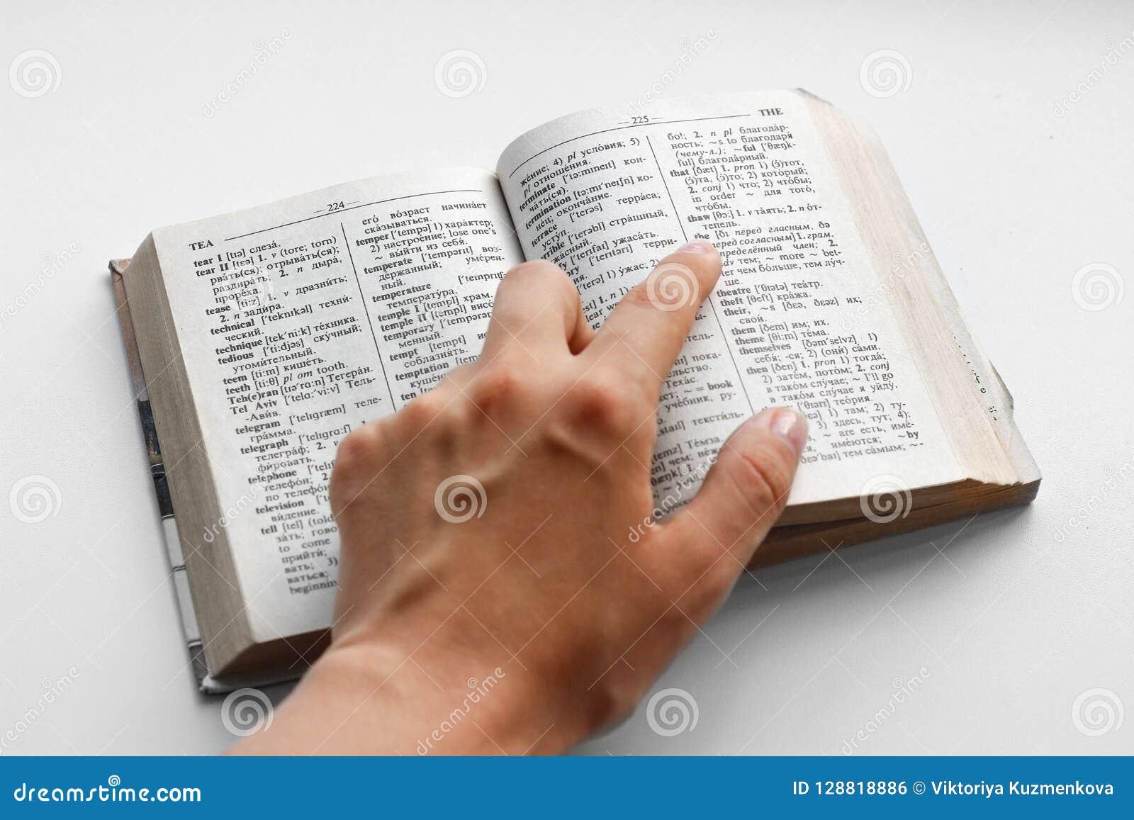 Räcka att peka fingret på den engelska ryska ordboken close upp