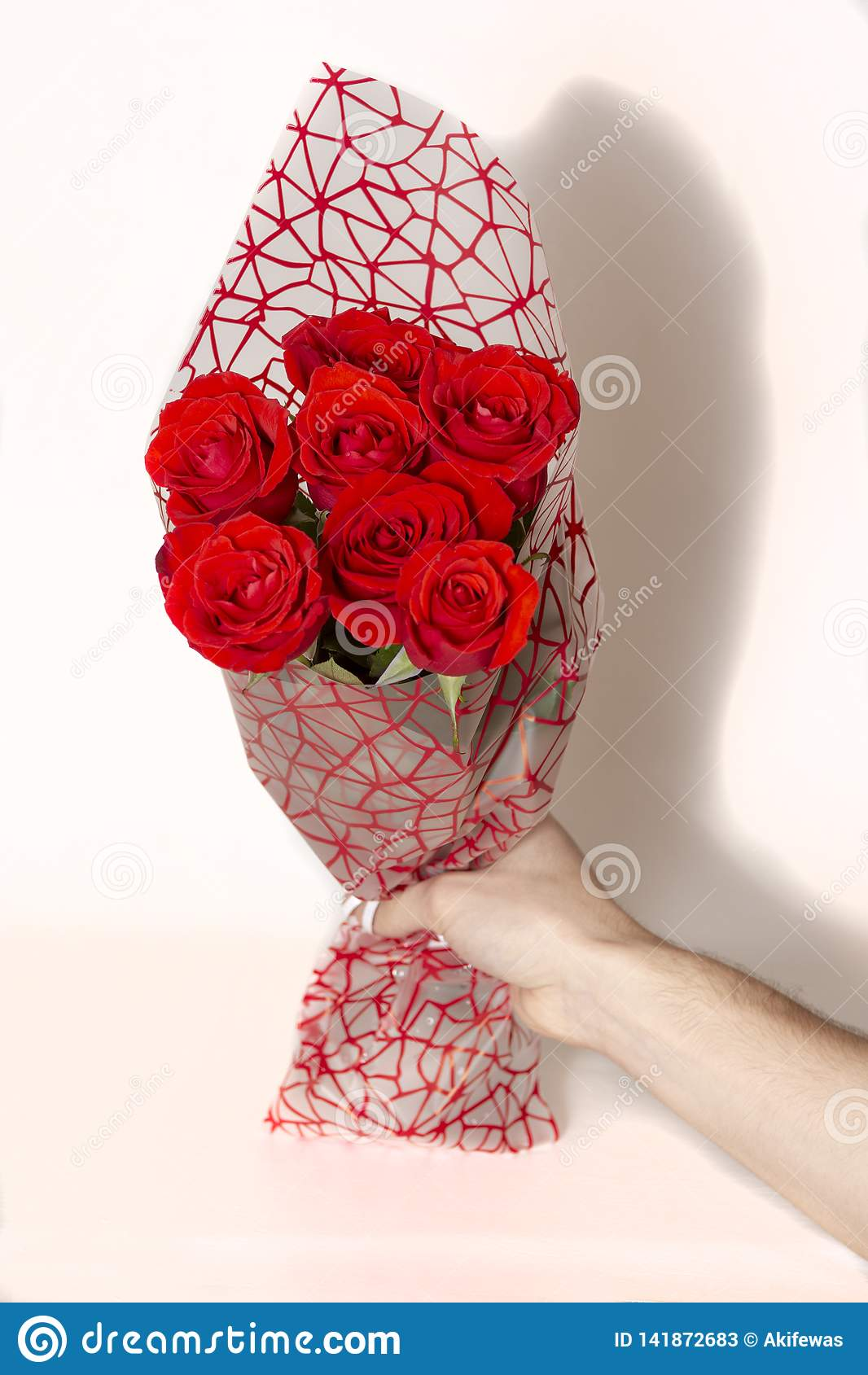 Räcka den hållande buketten av röda rosor över vit bakgrund