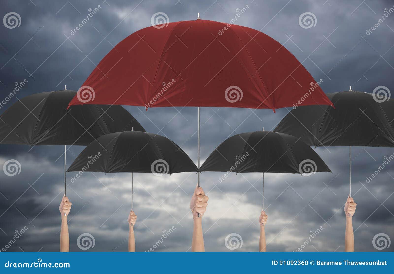 Räcka det hållande röda paraplyet som är olikt bland svart umbella