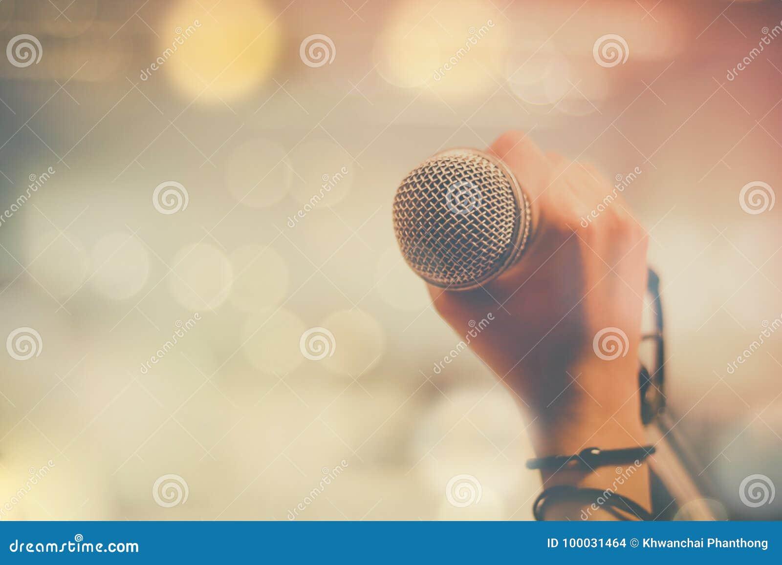 Räcka hållande mikrofon- och bokehbakgrund, begrepp som musikinstrumentet i studiorum