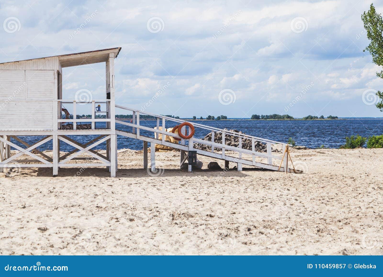 Räddningsaktionstation på den sandiga stranden på sommardag