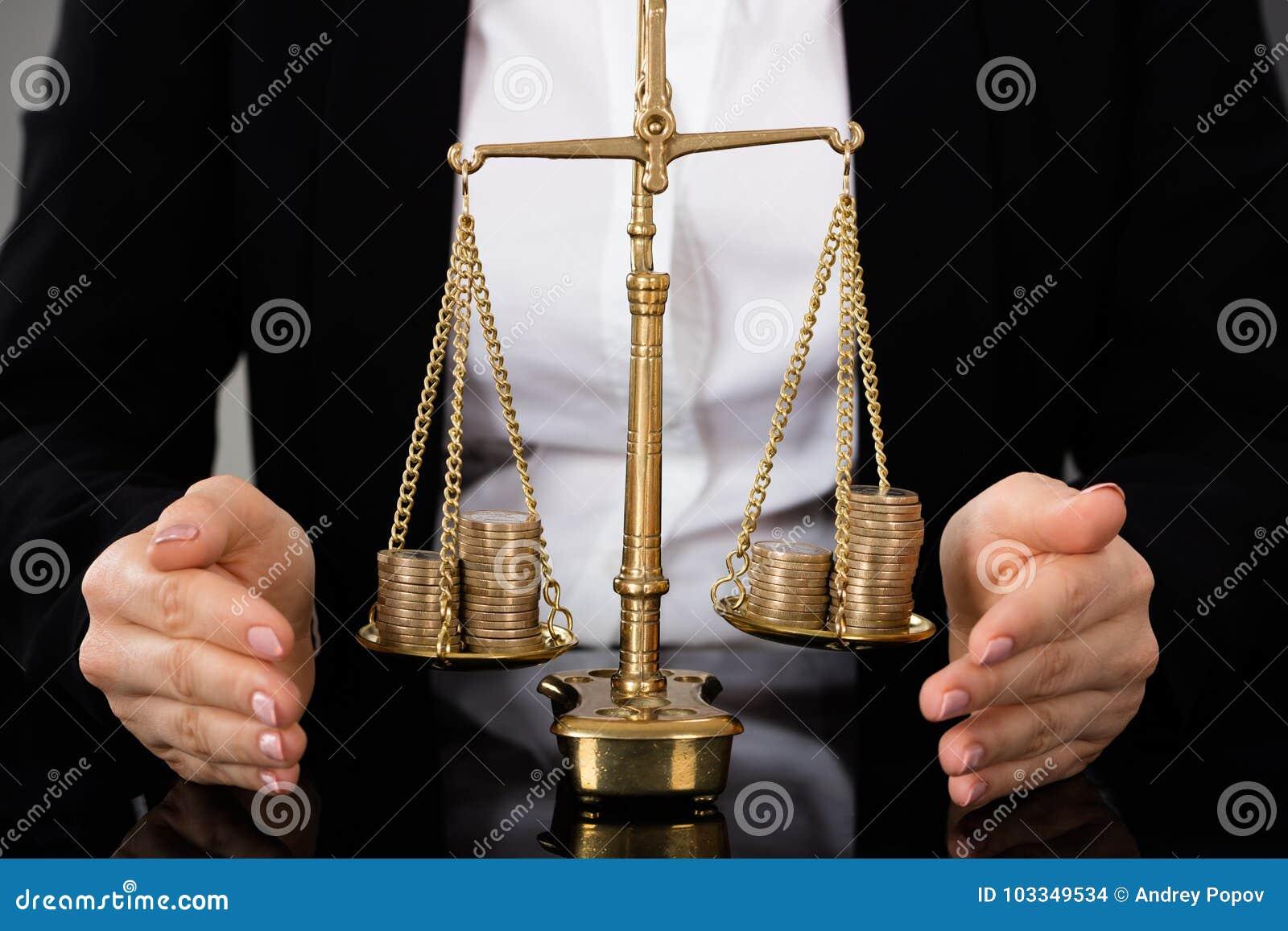 Rättvisa Scale With Coins för hand för advokat` s skyddande