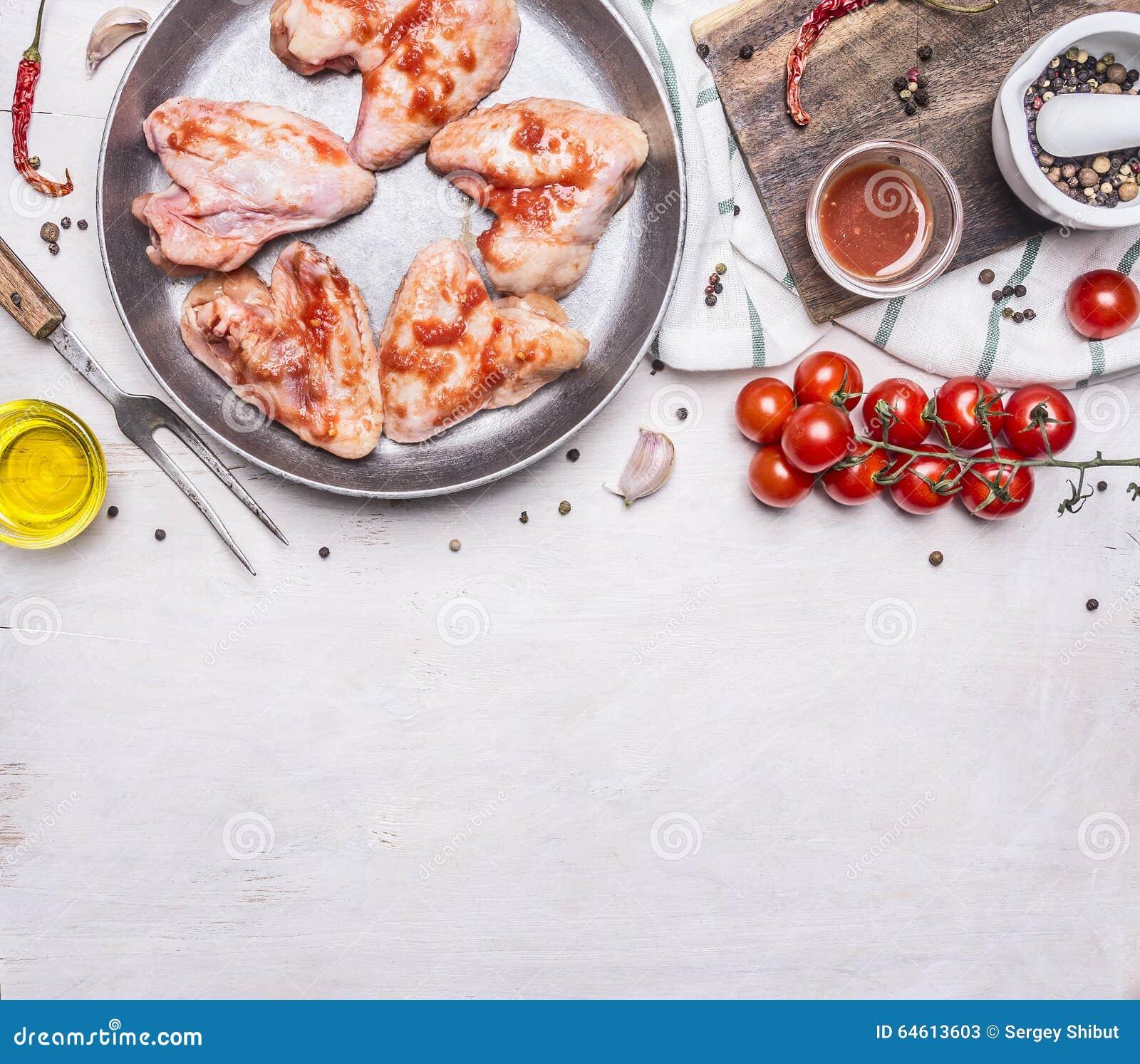 Rå fega vingar i grillfestsås i pannan, med för grönsak- och kryddaträlantligt bakgrund slut för bästa sikt upp