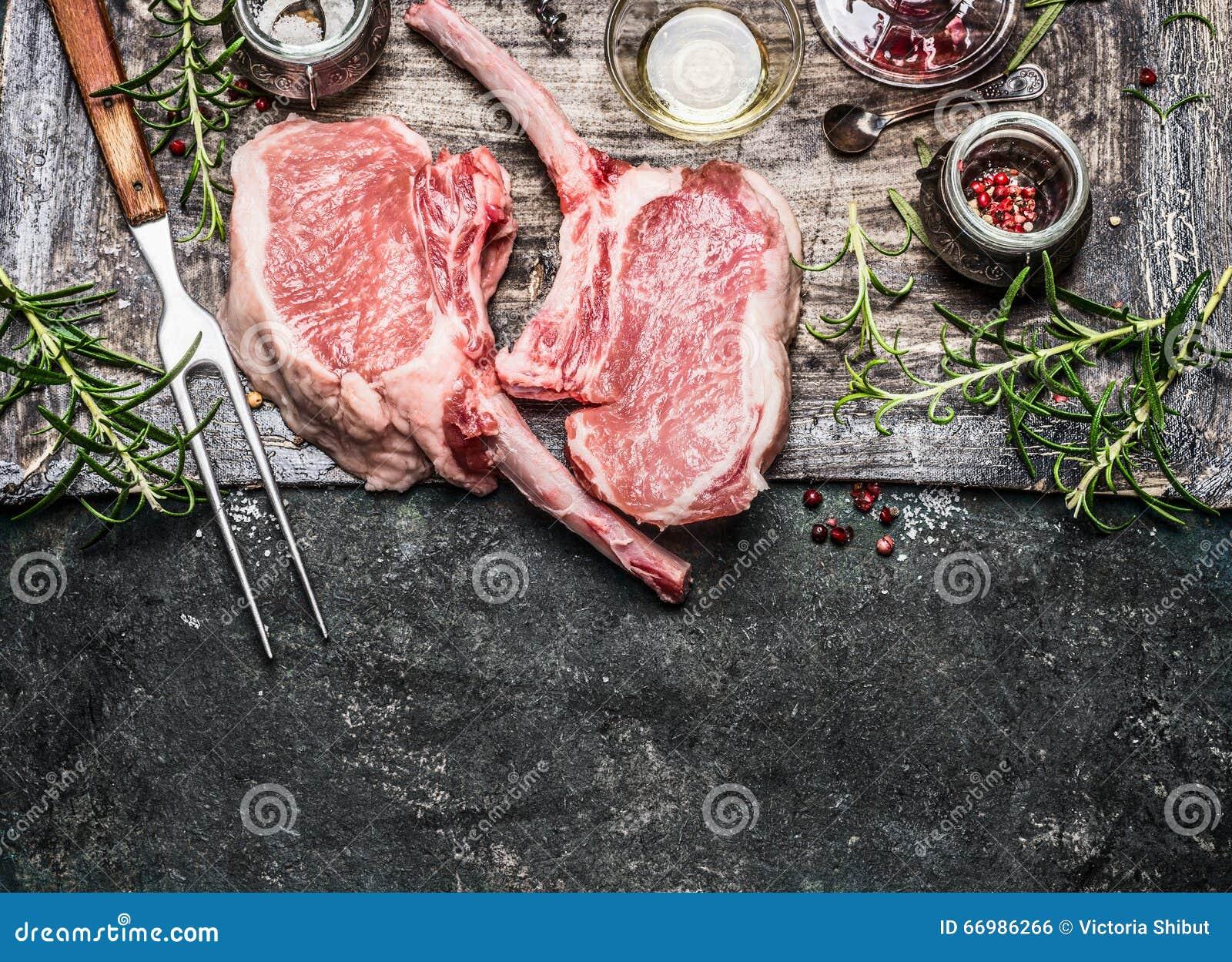 Rå fläskkotlettbiffar med köttgaffeln, olja och kryddor för galler eller matlagning på lantlig metallbakgrund, bästa sikt,