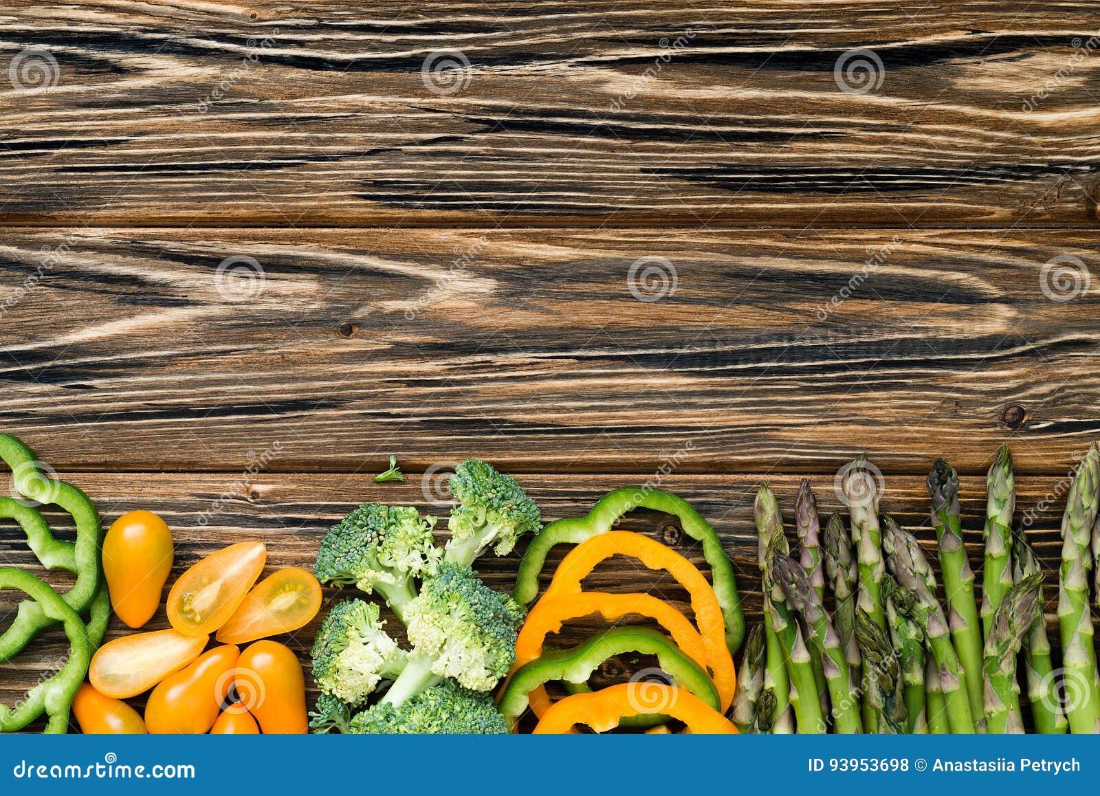 Rå gröna och gula veggies Lägenheten lägger på trätabellen
