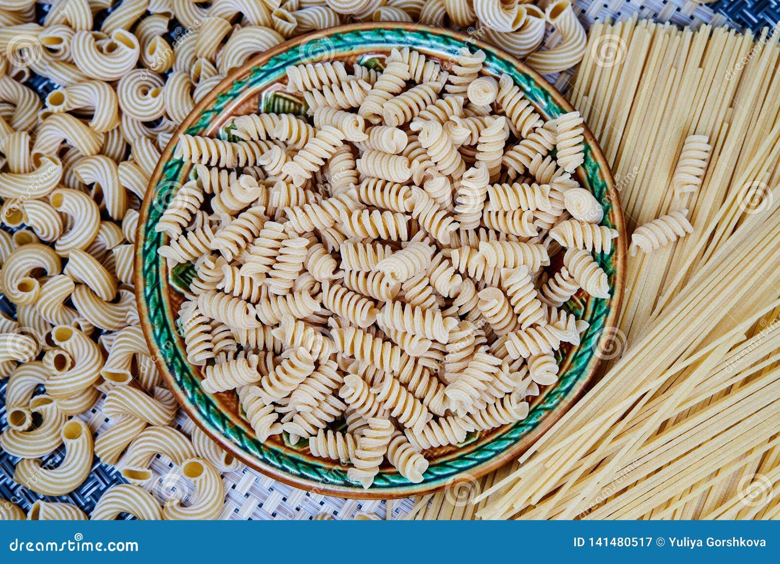 Rå hel-korn pasta i en platta på en vide- torkduk på tabellen Top beskådar