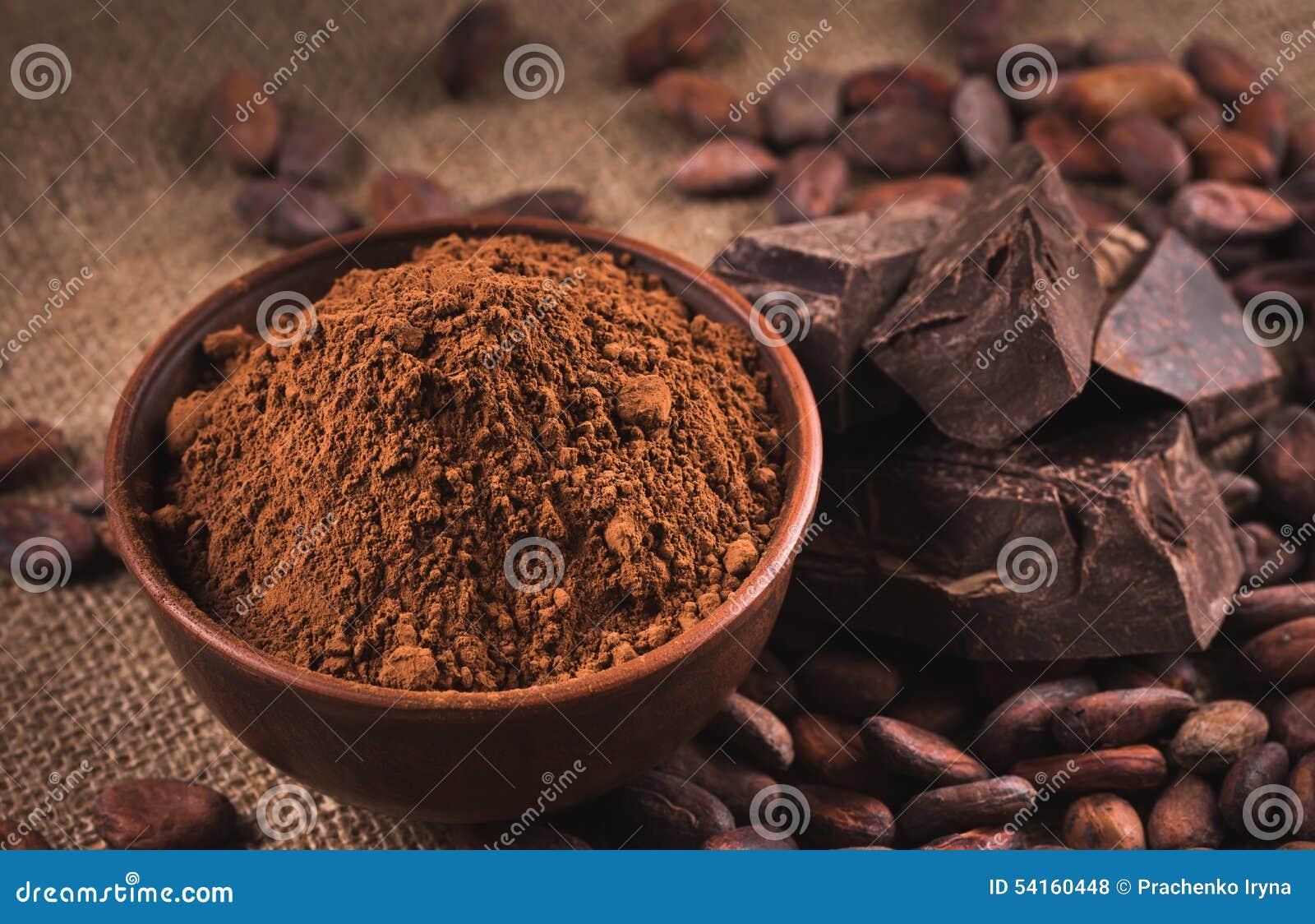 Rå kakaobönor, lerabunke med kakaopulver, choklad på säcken