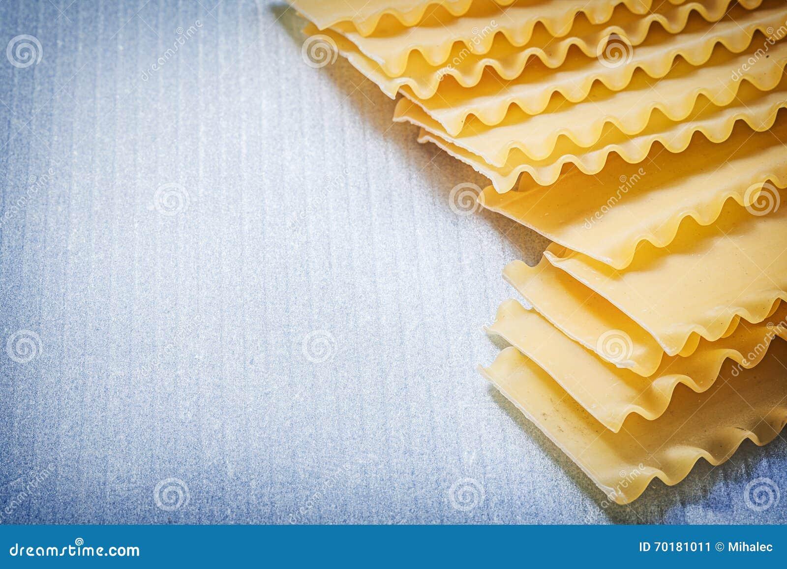 Rå lasagnepasta på blått ytbehandlar mat- och drinkbegrepp