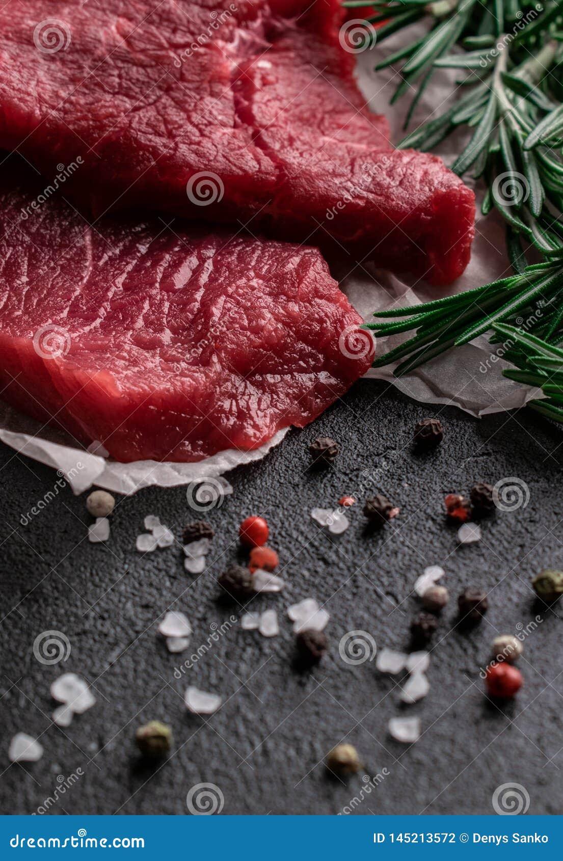 Rå nötköttbiff med rosmarinfilialer på pergamentpapper med peppar och att salta