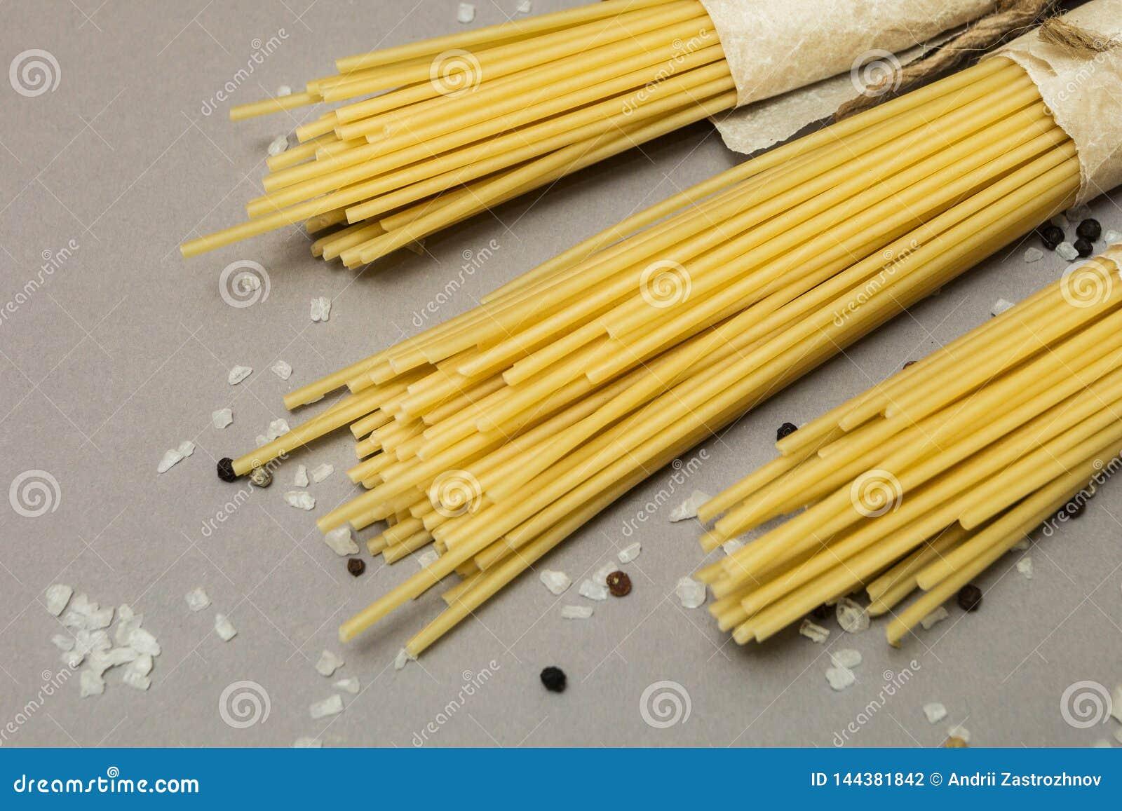 Rå pasta på en grå bakgrund i en lantlig packe Selektivt fokusera
