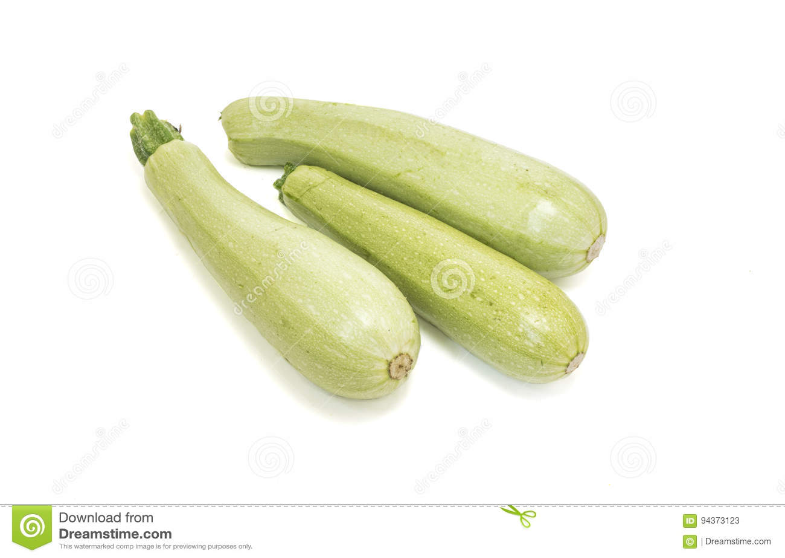 Rå zucchini som isoleras på vit
