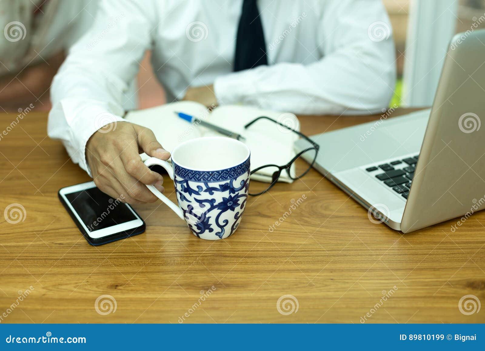 Rånar hållande kaffe för affärsmanhanden med mobiltelefonen och anteckningsboken