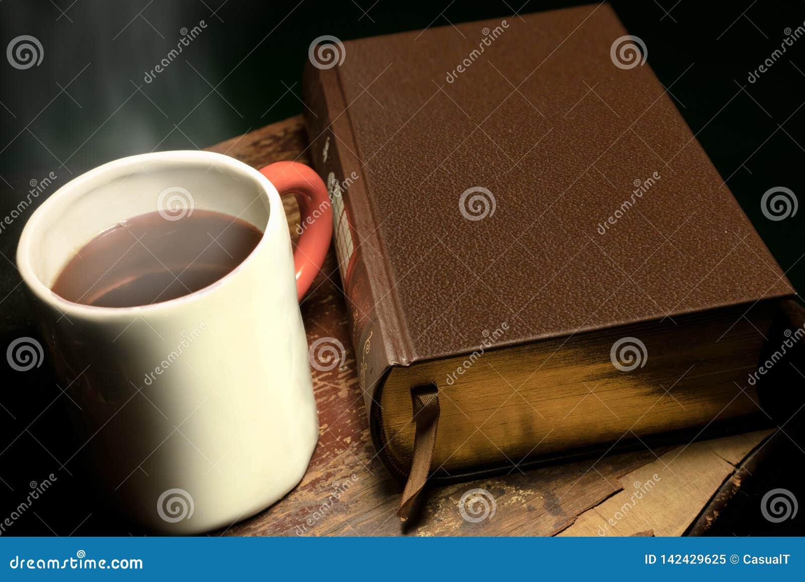 A rånar med kokhett te eller kaffe som förläggas bredvid en stor läder-destinerad bok, på en gammal och sliten trätabell