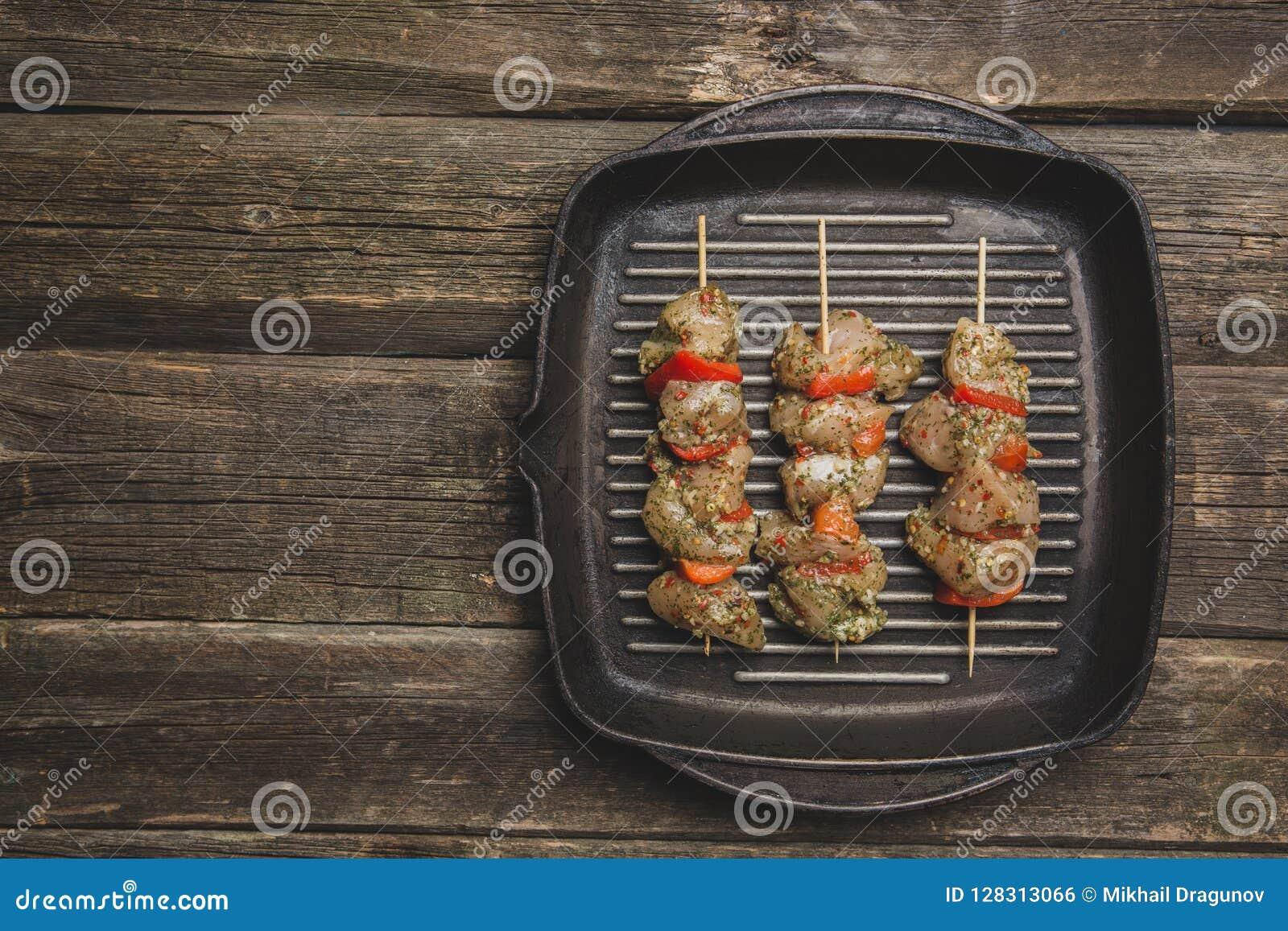 Rått chiken kött med grönsaker på steknålar på gallergjutjärnpannan
