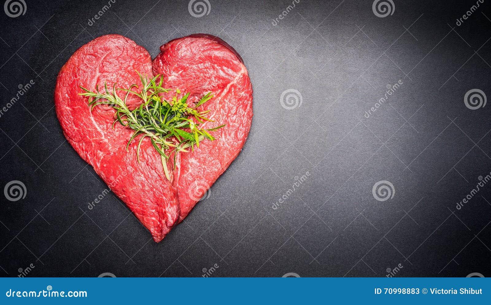 Rått kött för hjärtaform med örter på mörk svart tavlabakgrund Sund livsstil eller begrepp för organisk mat