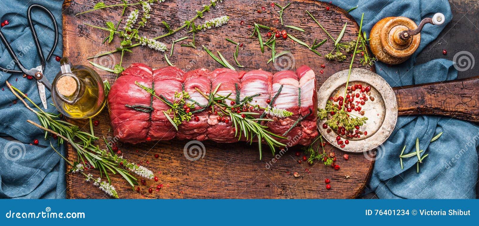 Rått steknötkött med örter som binds med ett rep med matlagningingredienser, olja och kryddor på lantlig bakgrund, bästa sikt