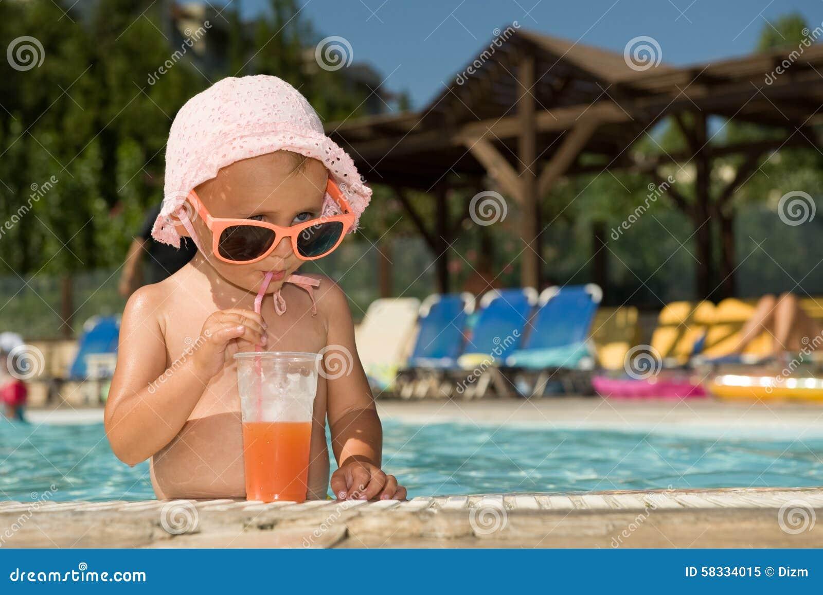 f96ffce43114b0 Petit bébé drôle avec les lunettes de soleil et le cocktail dans la piscine  extérieure