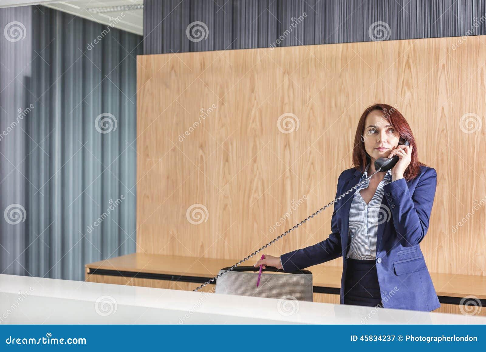 Réceptionniste parlant au téléphone dans le bureau image stock