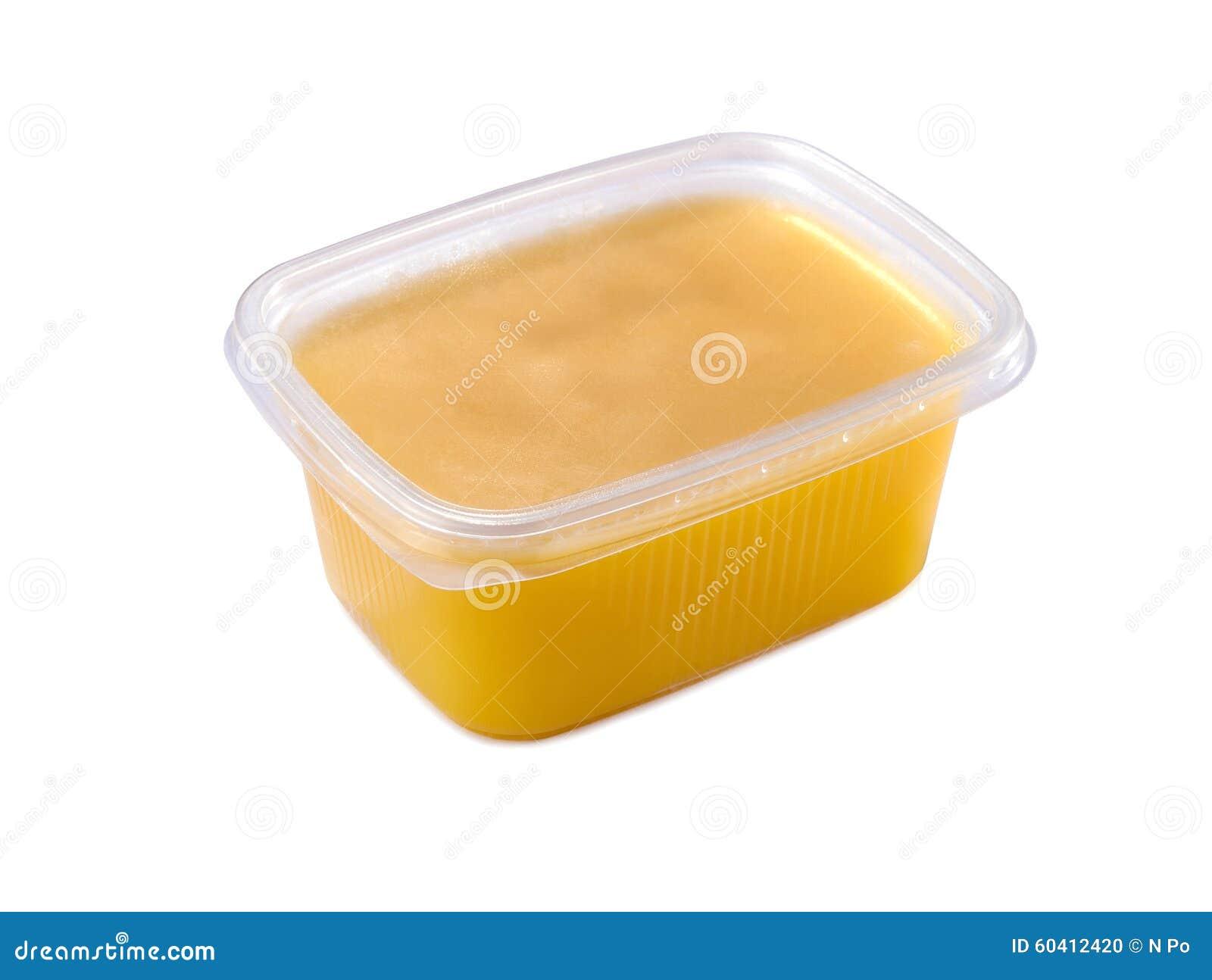 Récipient en plastique avec du beurre de ghee d isolement sur le blanc