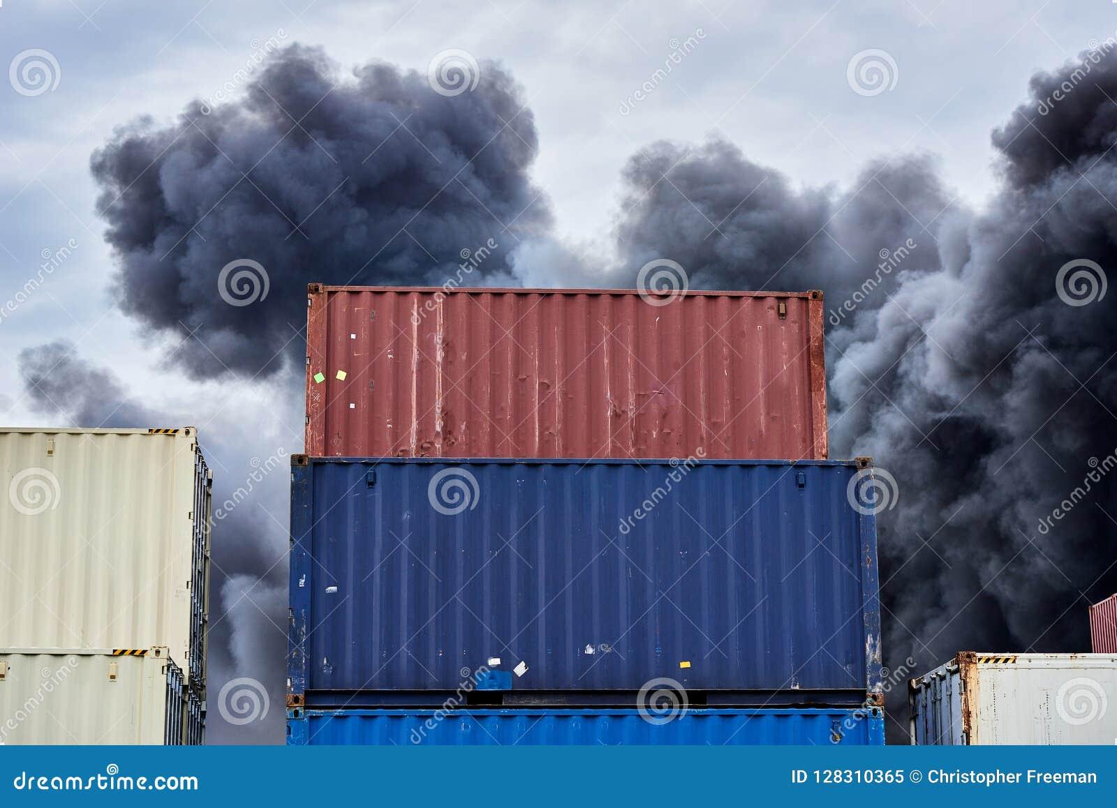 Récipients d expédition empilés dans le stockage avec de des volutes de la fumée toxique noire d un feu contre un ciel bleu