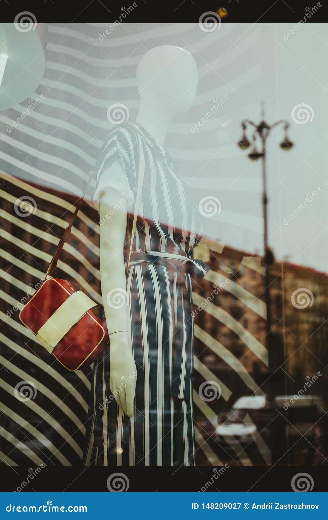 Réflexion de la ville dans la fenêtre d un magasin de mode avec un mannequin