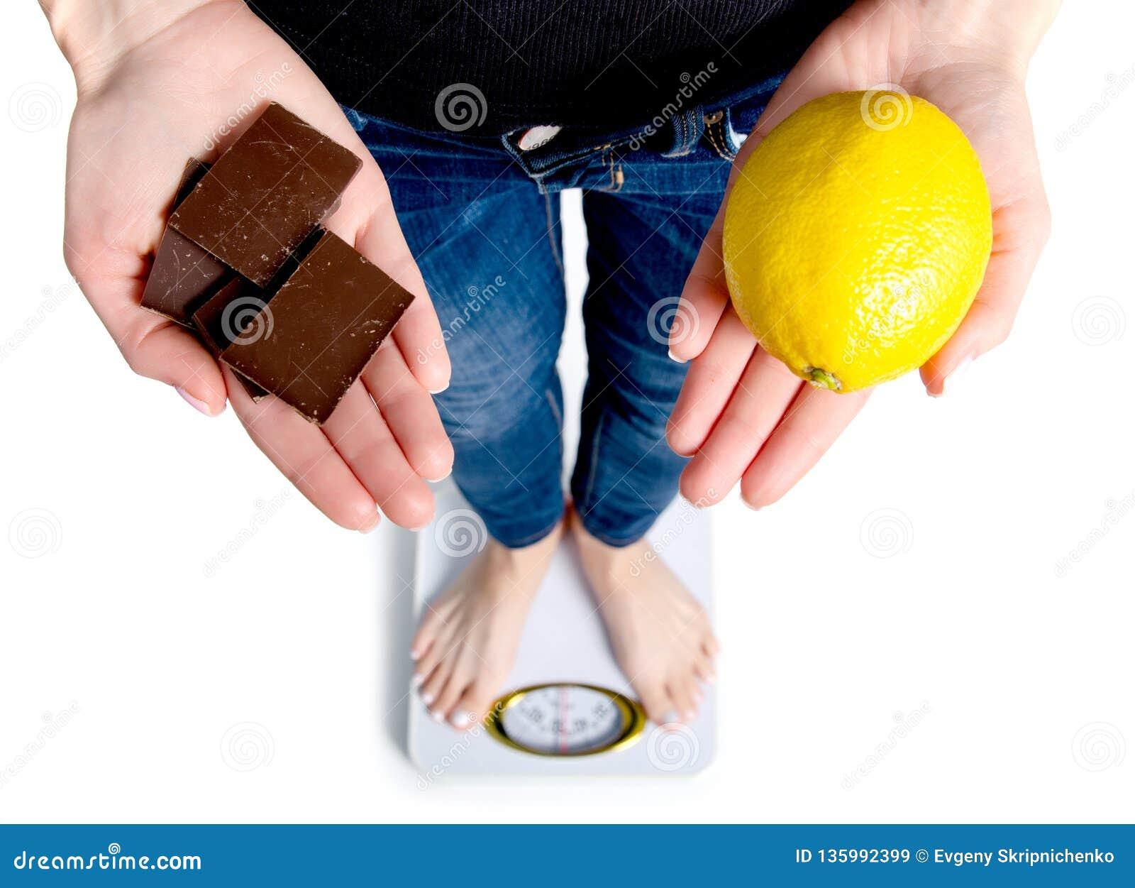 Régime Poids corporel de mesure de femme sur la balance tenant le chocolat et le citron