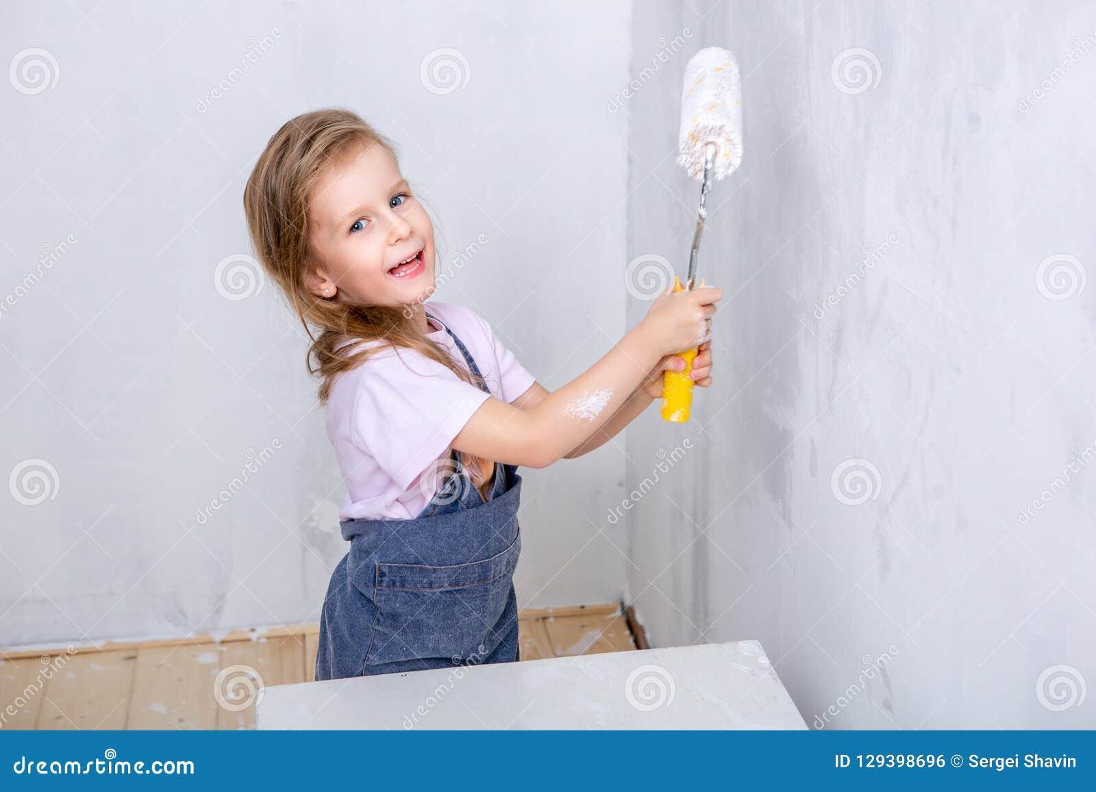 Réparation dans l appartement La mère et la fille heureuses de famille dans les tabliers peignent le mur avec la peinture blanche