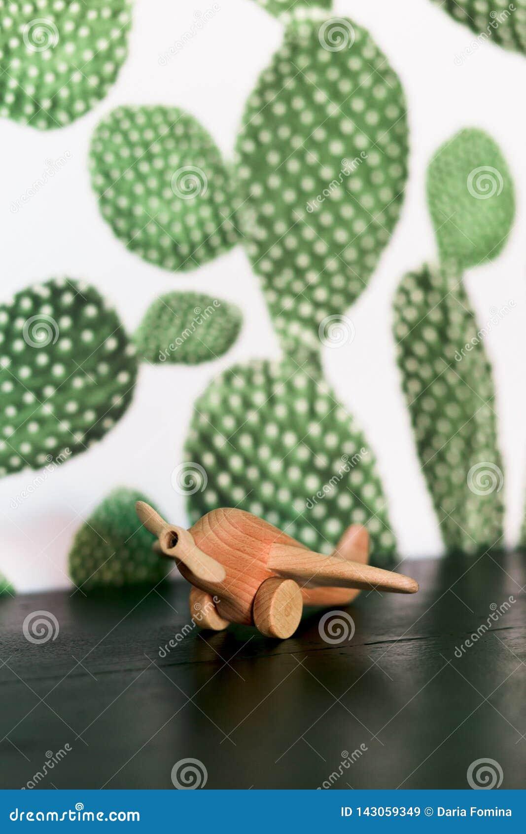Rétro avion en bois de jouet sur la table avec le fond de cactus