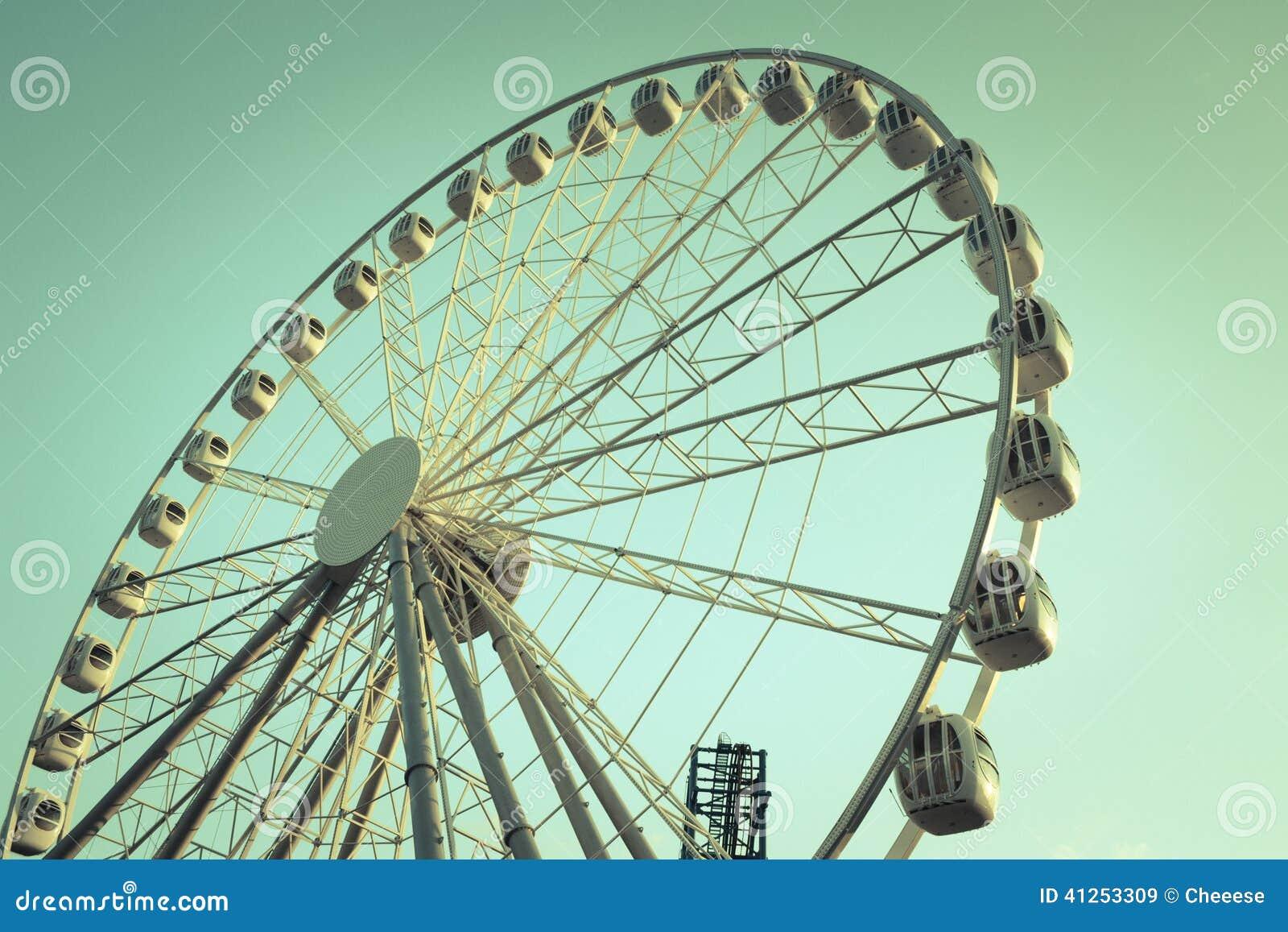 Rétro image de style d une roue de ferris contre le ciel bleu