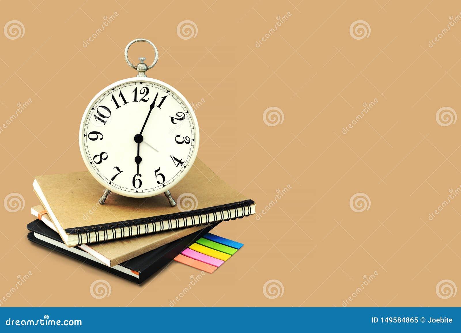 Réveil empilé sur le carnet brun et noir avec un papier de note de post-it D isolement sur le fond brun avec l espace et l agrafe
