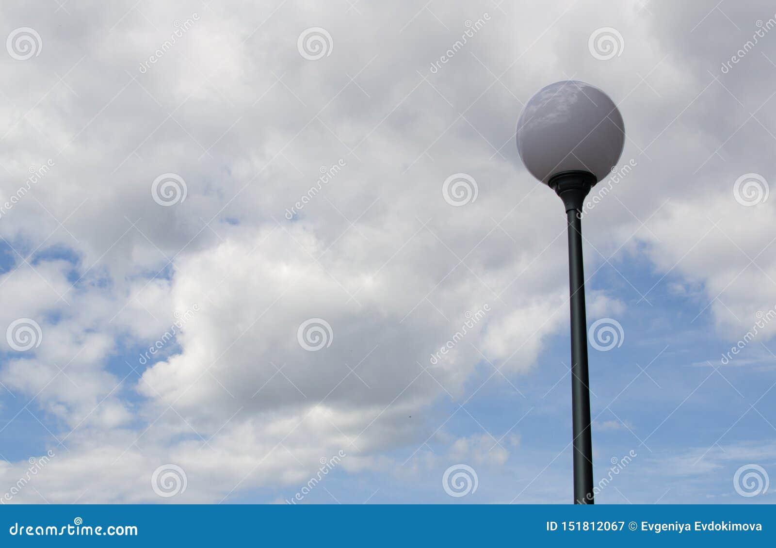 Réverbère rond contre un ciel nuageux