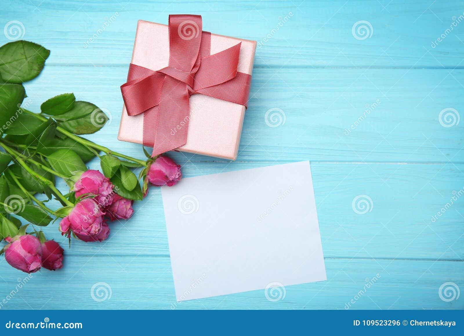 Róże, prezenta pudełko i opróżniają kartę na drewnianym tle