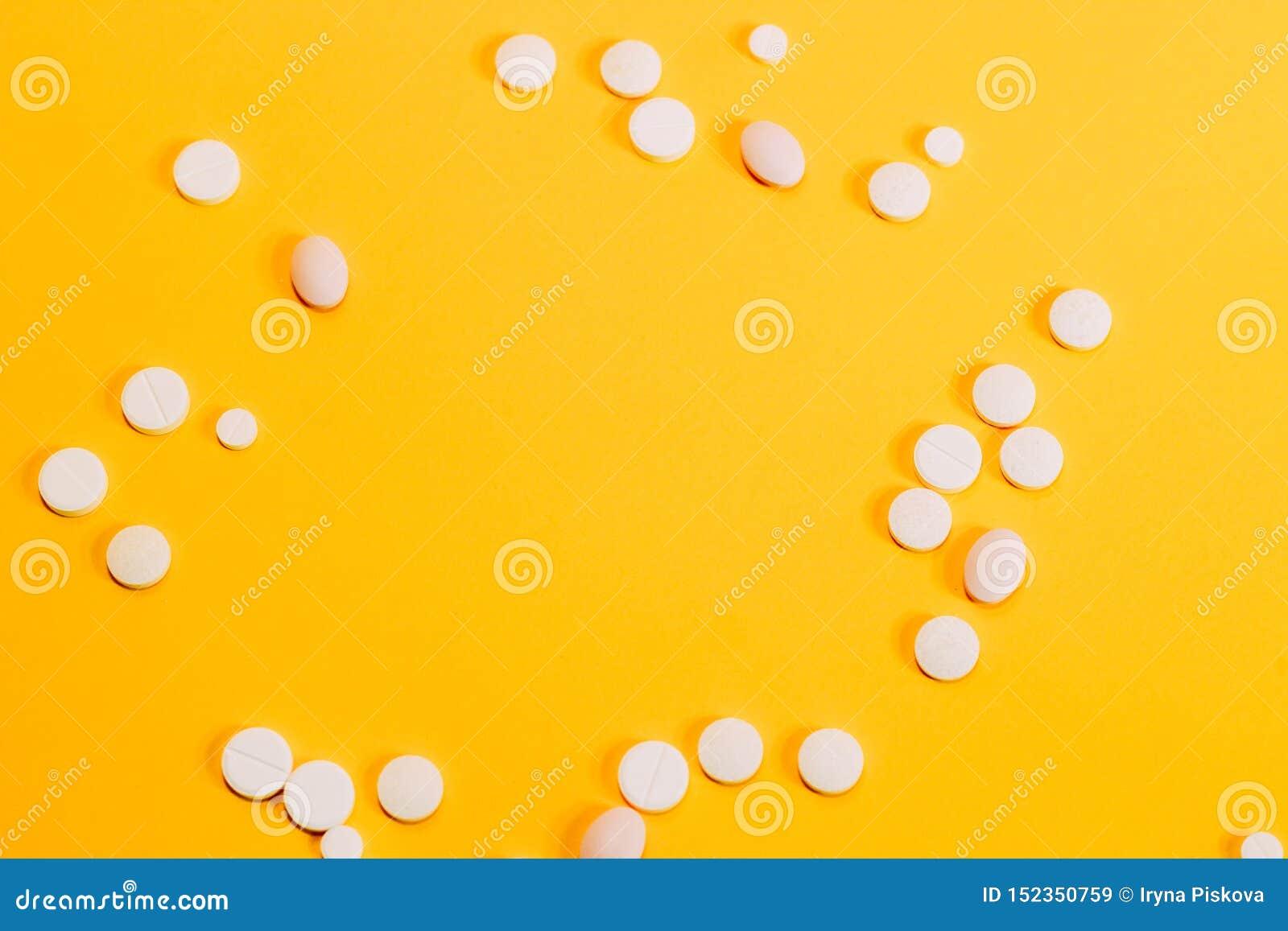 Różne pigułki i witaminy rozpraszają na żółtym tle Przestrze? dla teksta