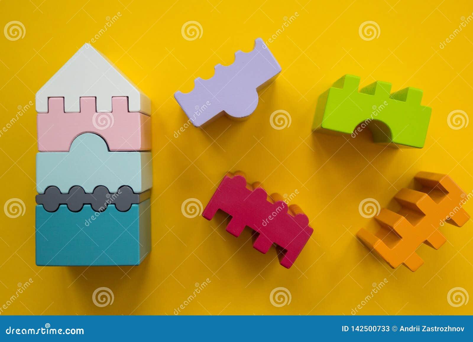 Różnobarwni drewniani bloki - mieści odosobnionego na żółtym tle