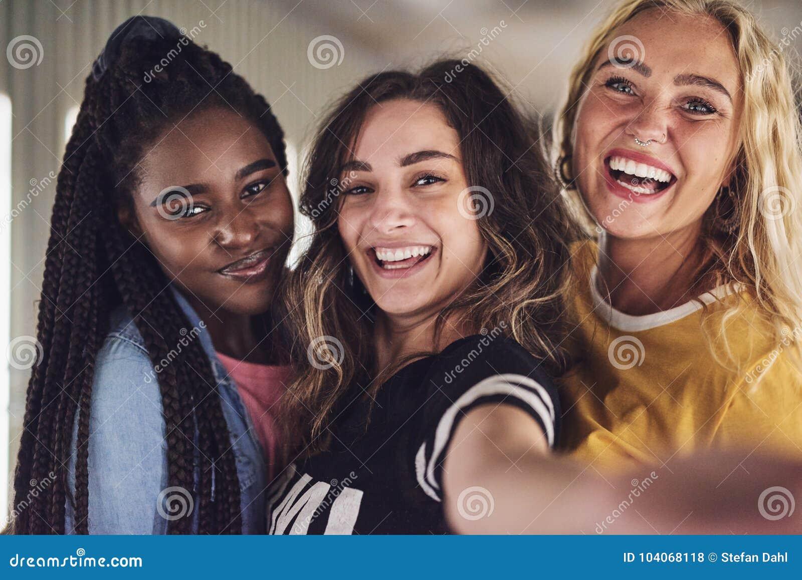 Różnorodna grupa młodzi żeńscy przyjaciele bierze selfie wpólnie