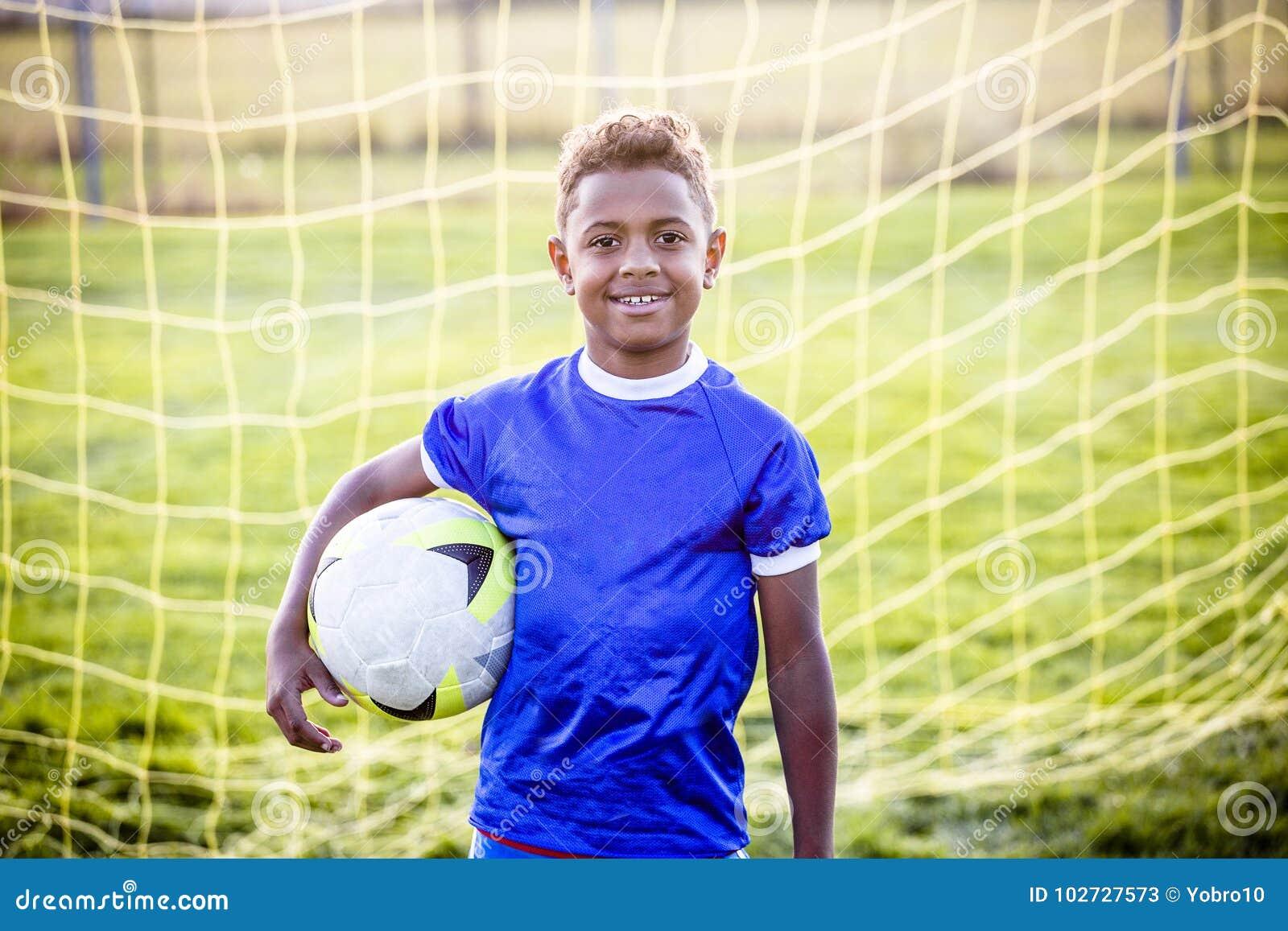 Różnorodna młoda chłopiec na młodości piłki nożnej drużynie